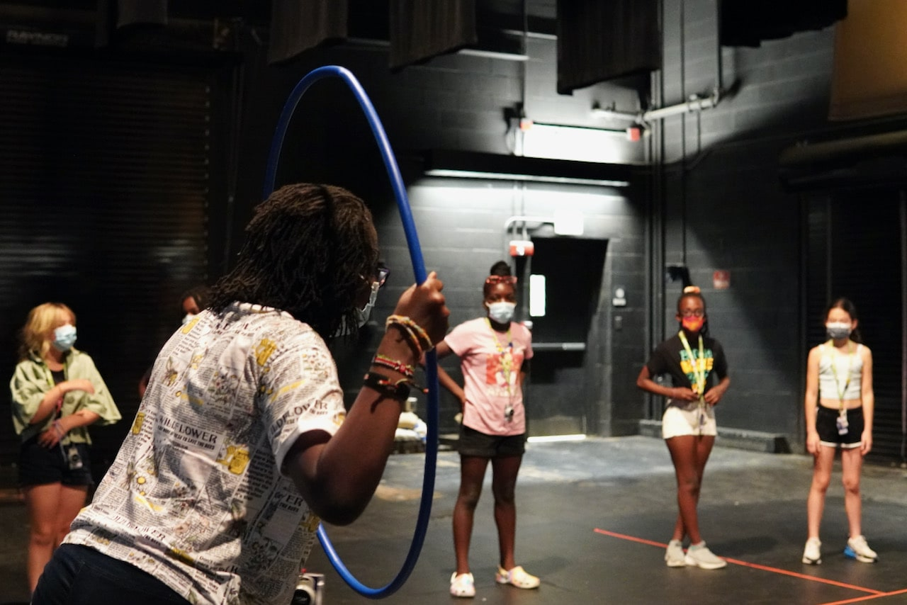 A student holds up a hula hoop acting like it's a window as other students look on