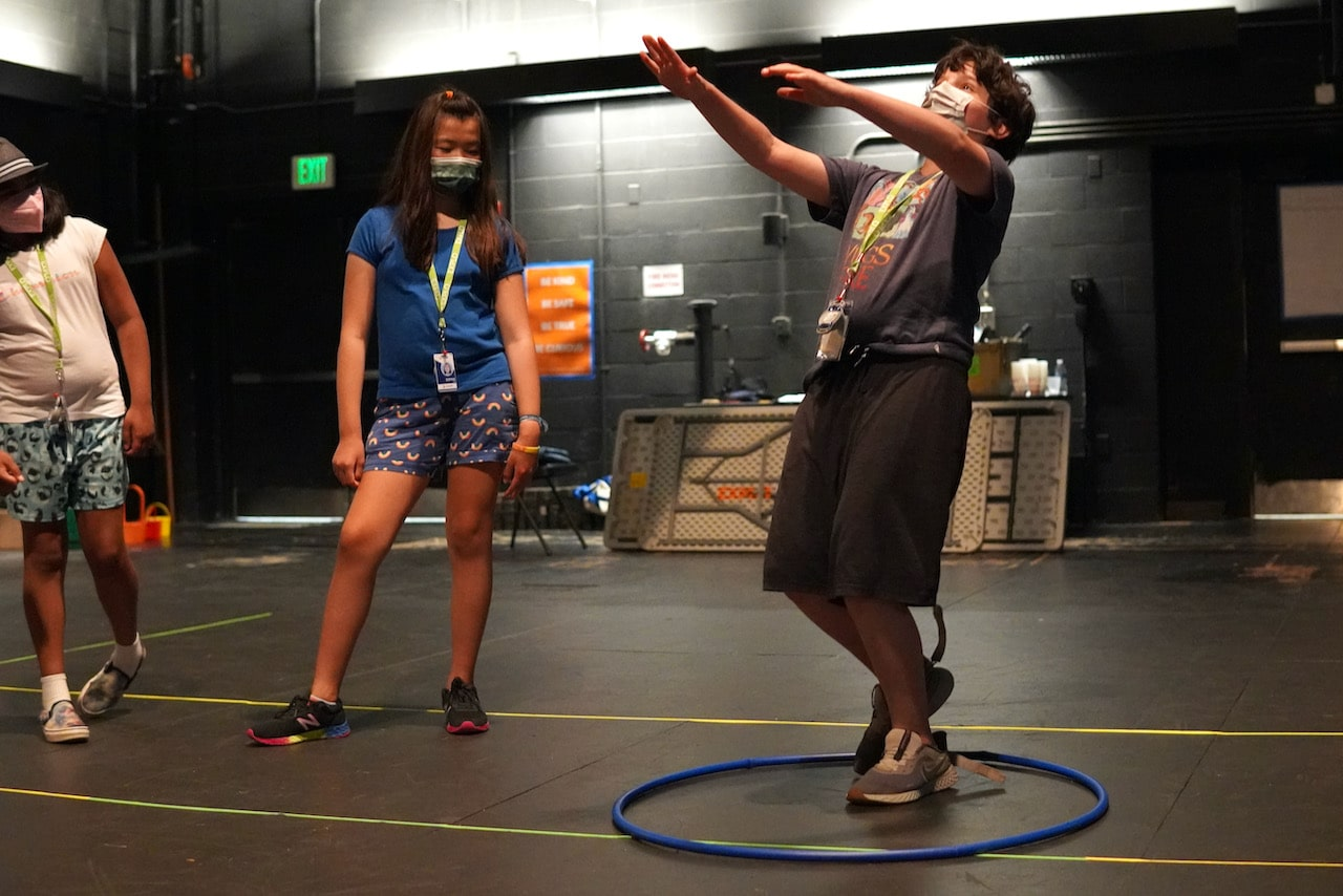 A student stands in a hula hoop while leaning backwards with both arms outstretched