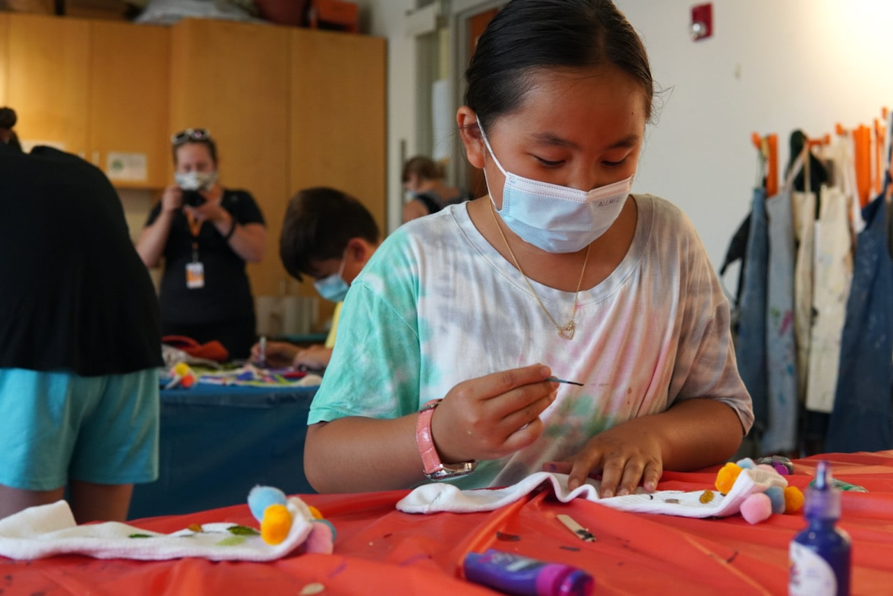 A student concentrates while painting on a pair of socks