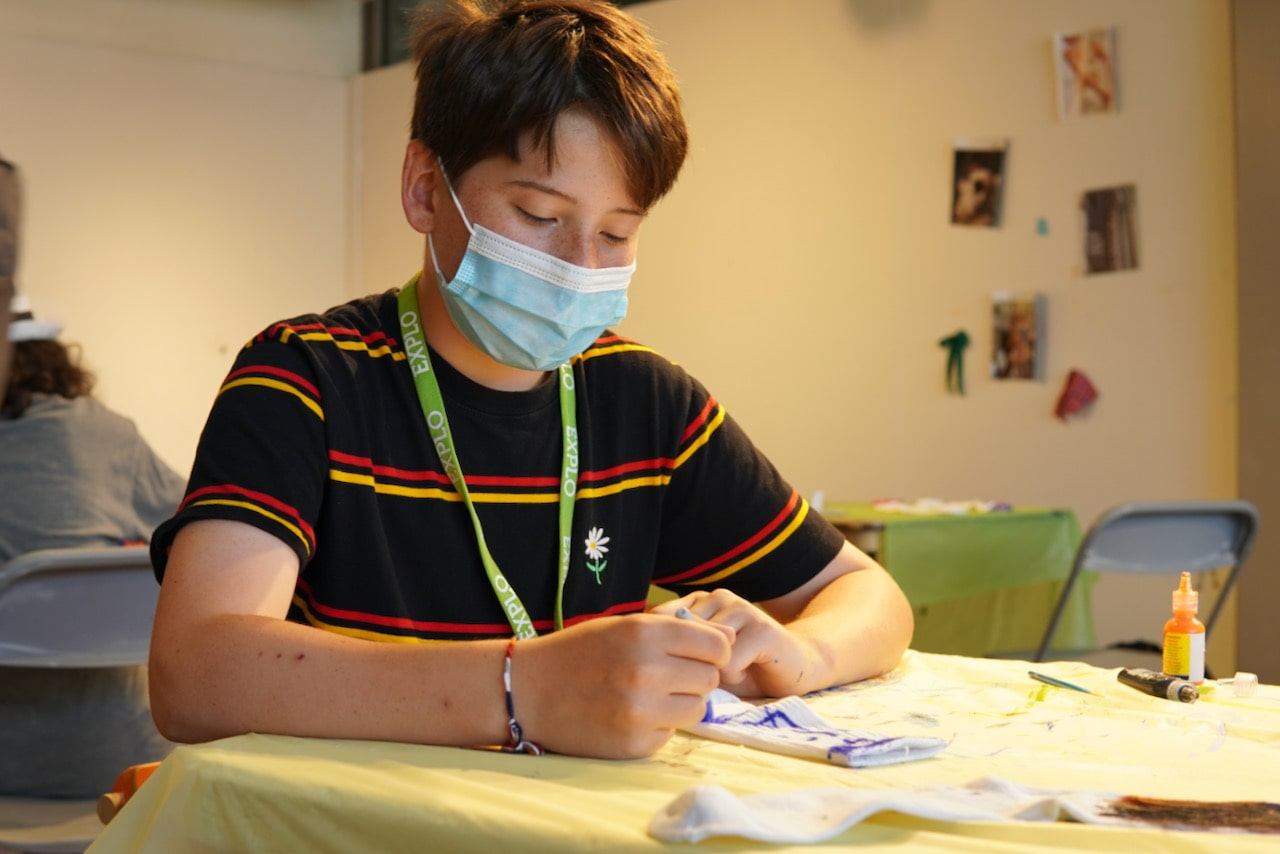 A student concentrates while drawing with sharpie on a white pair of socks