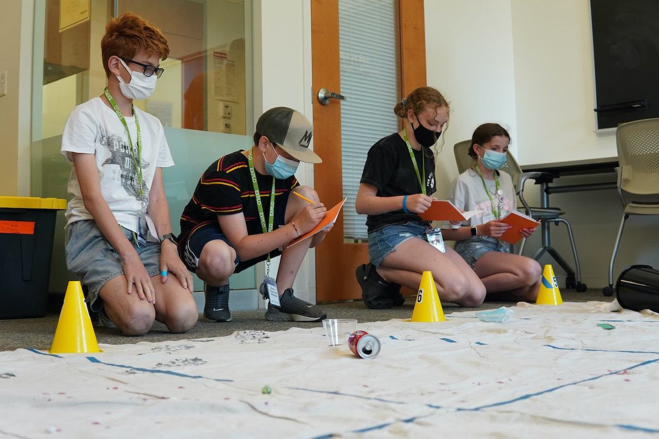 Four students sit on the floor and take notes about their crime scene