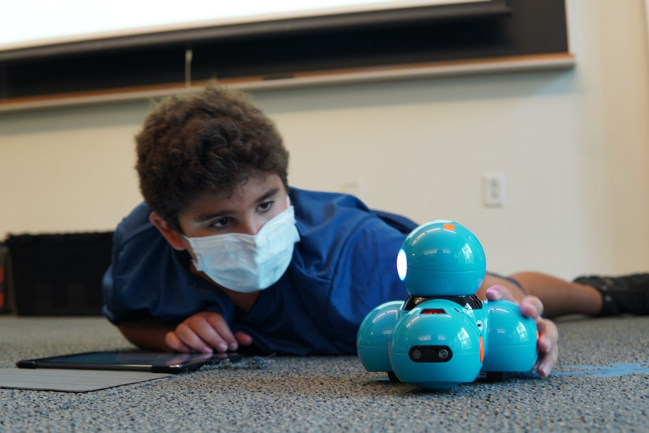 A student lies on the floor while moving a Dash Robot closer to him