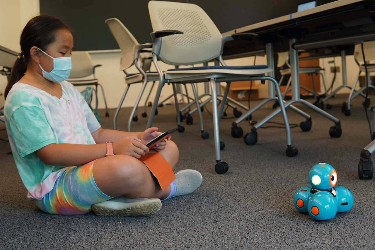 A student sits on the floor while using an iPad to move a Dash Robot around on the floor