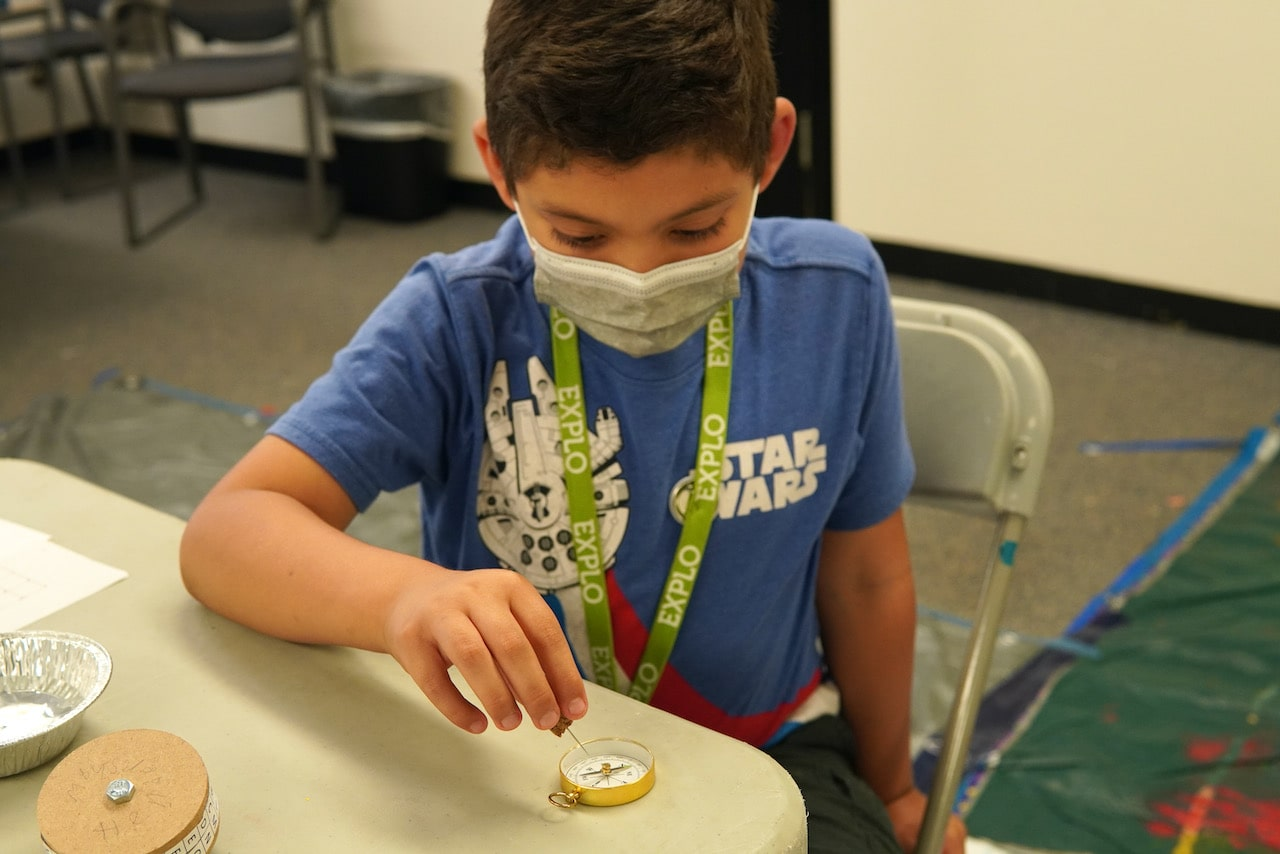 A student holds a magnet over a compass