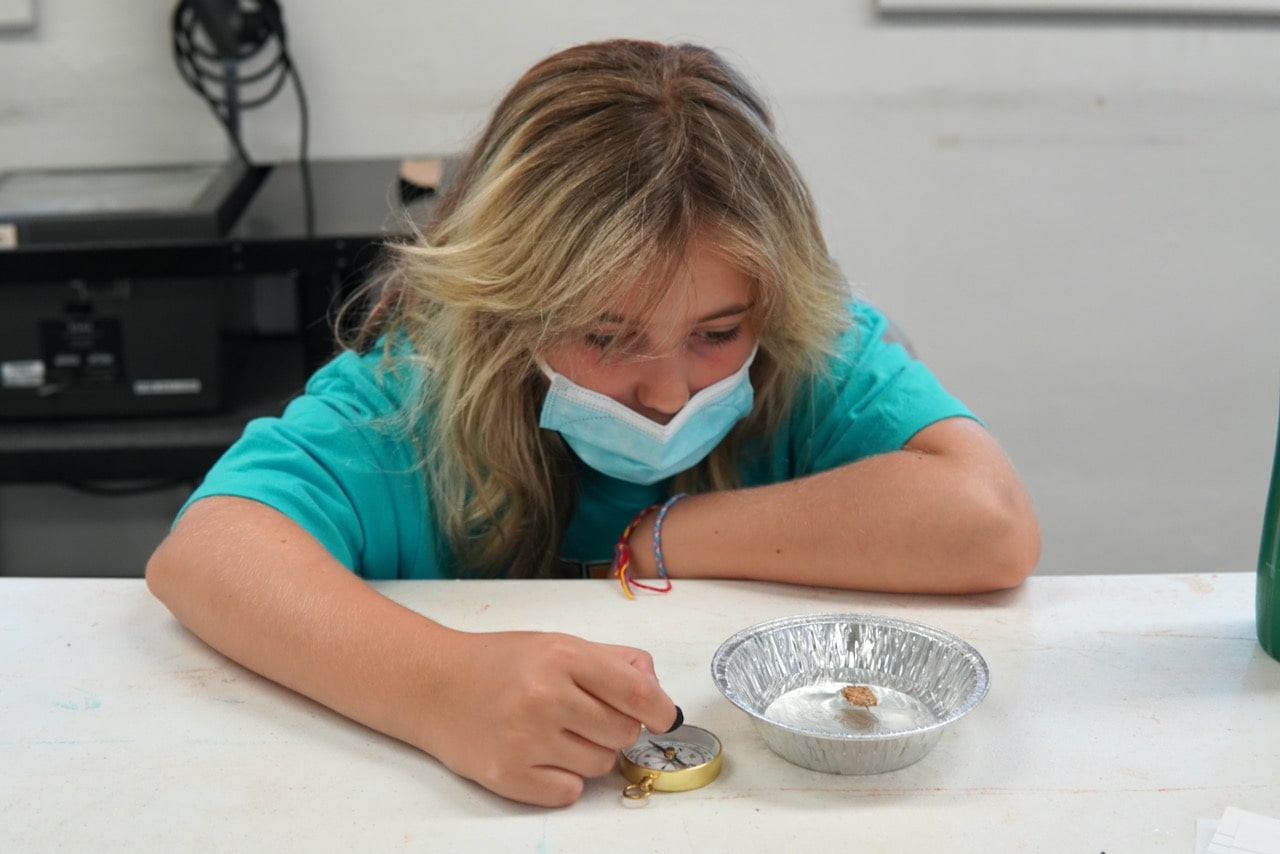 A student leans on the table and holds a magnet over a compass next to a tin full of water