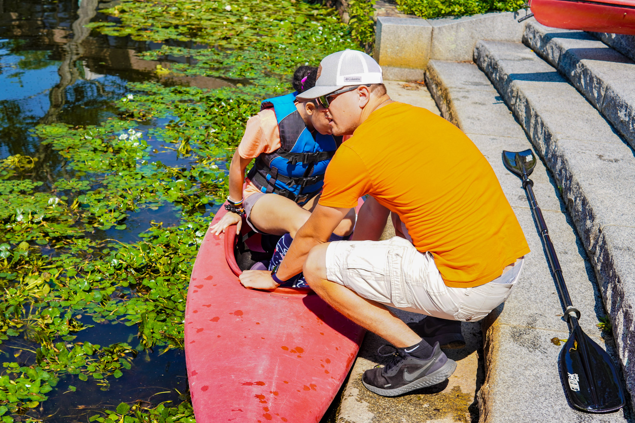 Teacher helps student in and out of the kayak for proper saftey