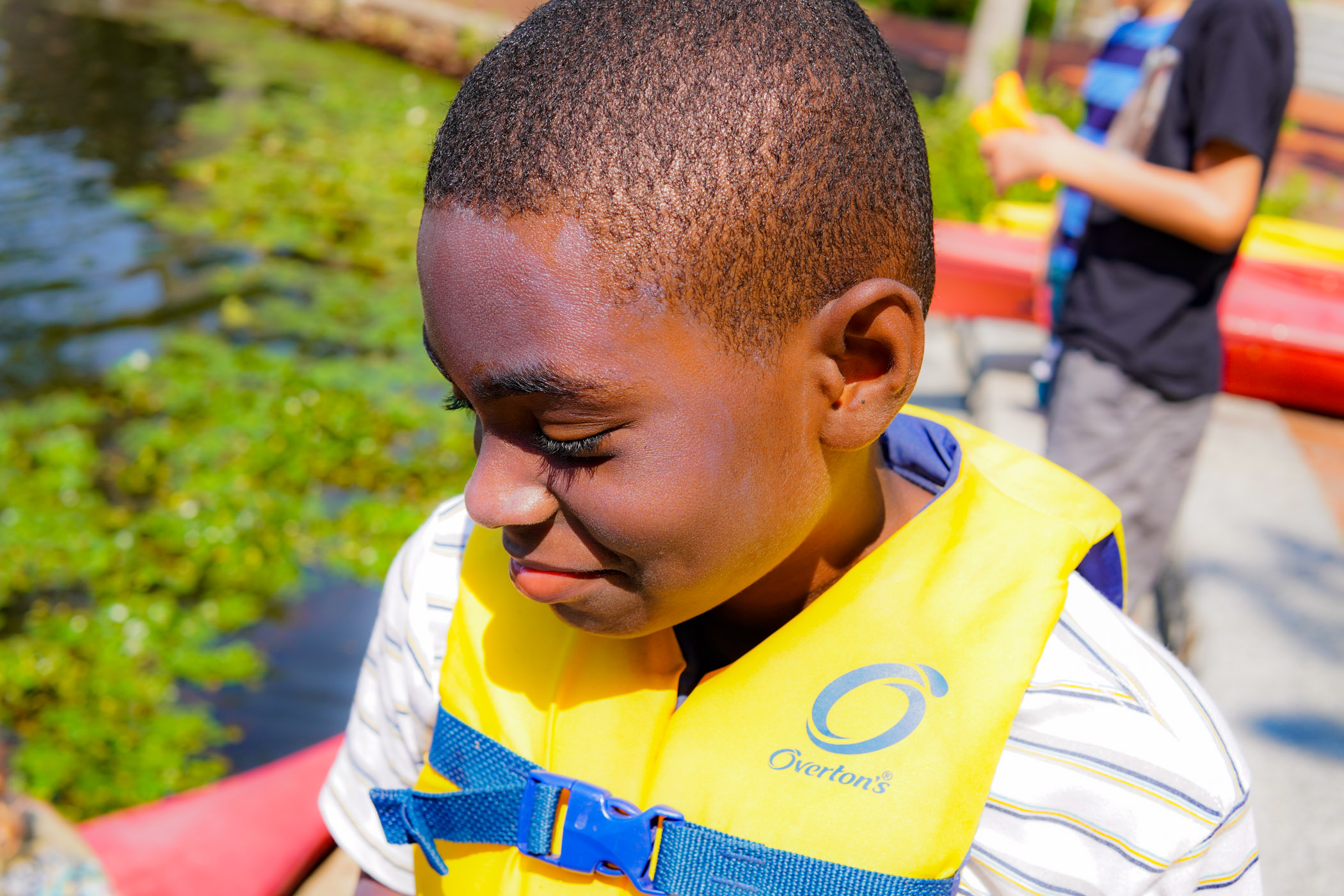 A student is eager to get started in kayaking on the pond