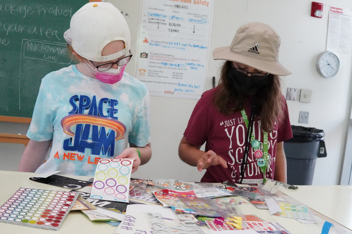 Two students gathering around the colorful stickers in gems for the right ones to decorate their boxes with