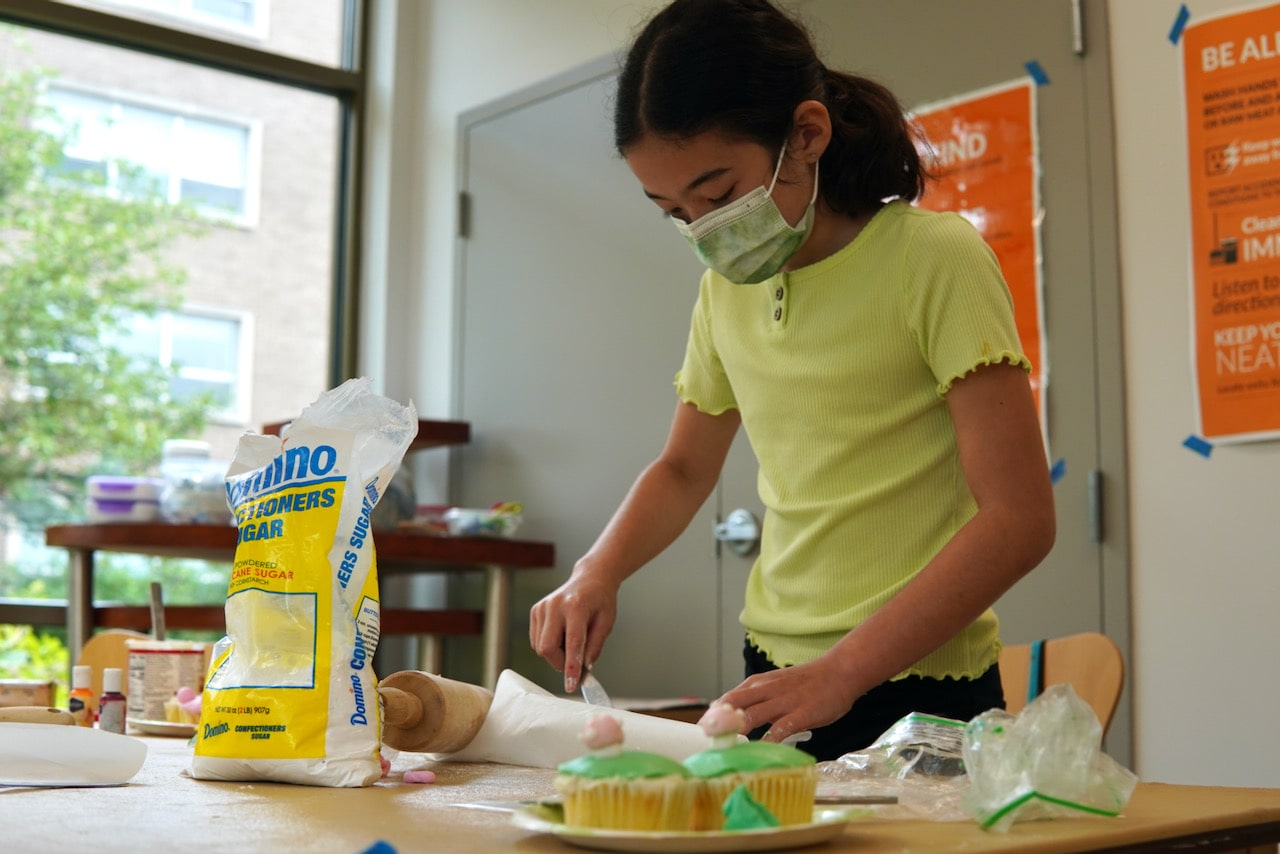 A student stands while using a knife to spread icing on a cupcake