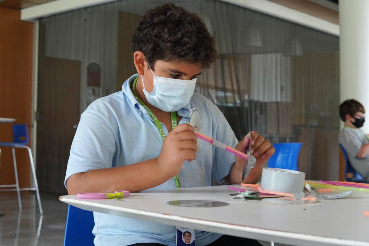 A student concentrates while duct taping two straws together