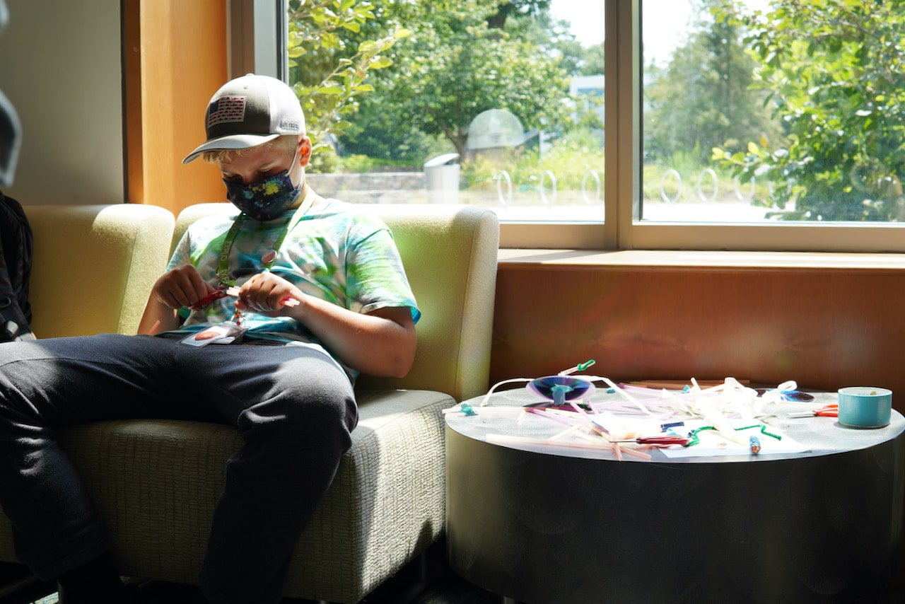 A student sits on a couch by a window with a table of materials sitting next to him