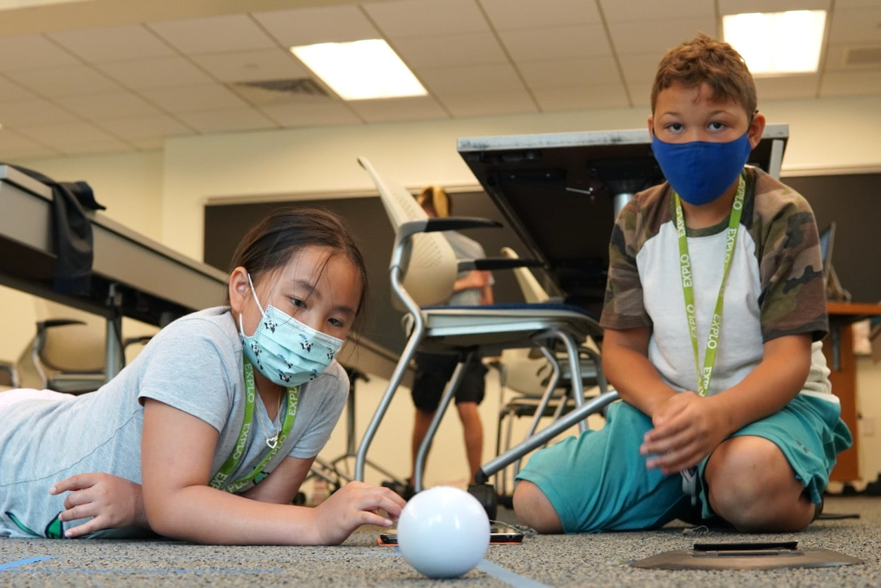 Two students sit on the floor while looking at a Sphero robot