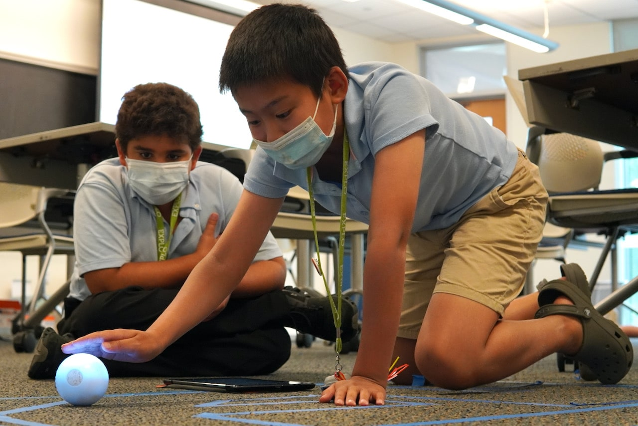 One student sits on the floor and uses an iPad while another student kneels and moves a sphero robot