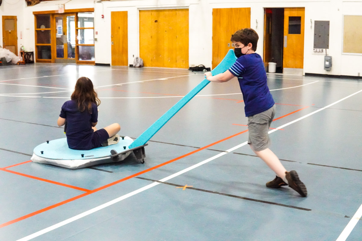 One student pushes another in a hovercraft across the floor