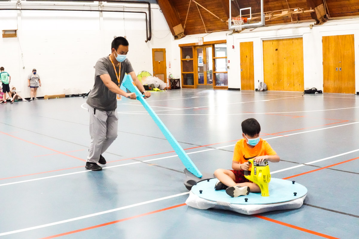 An EXPLO staff member pushes a student in a hovercraft across the floor