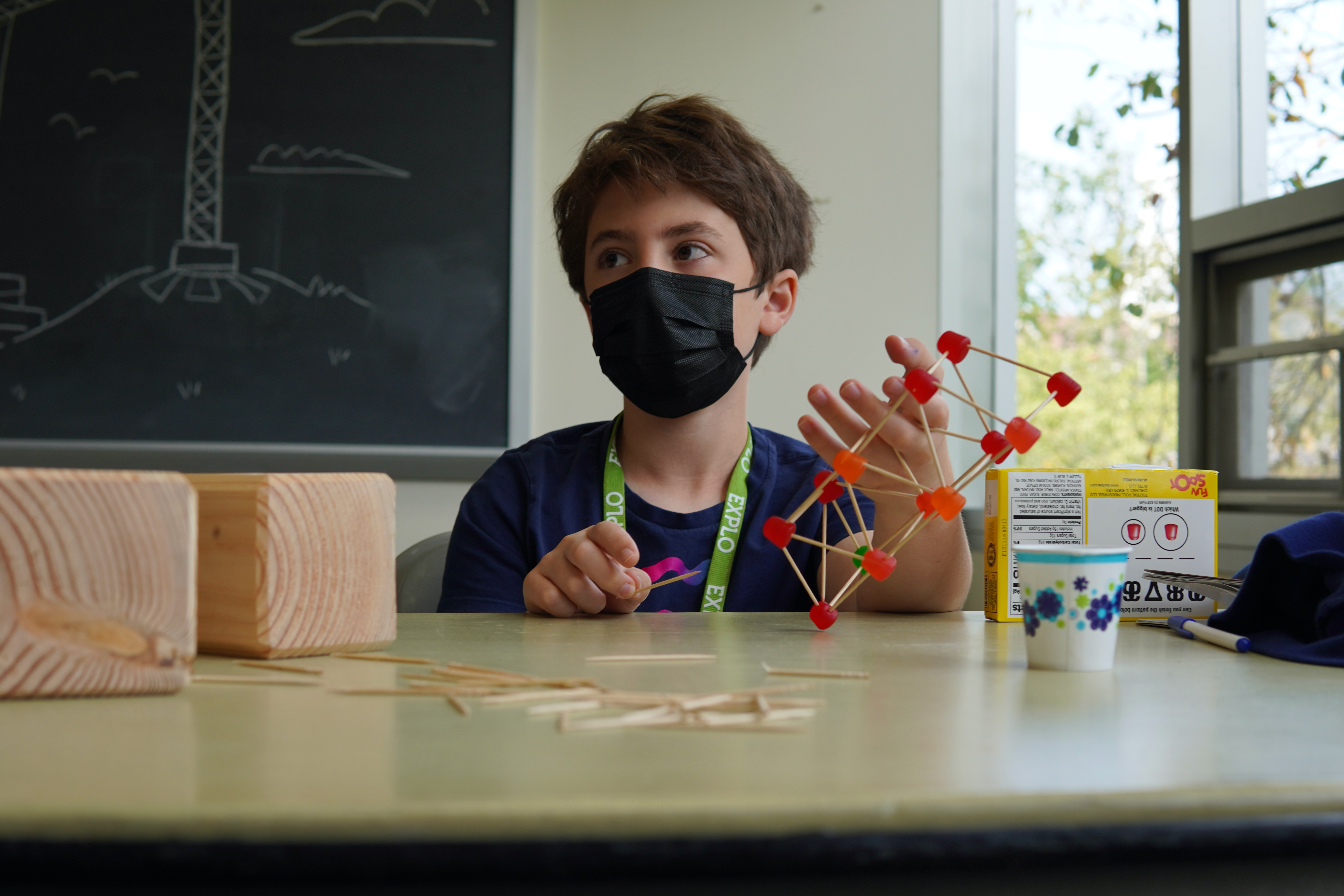 A student sitting at a desk holds a bridge model he made