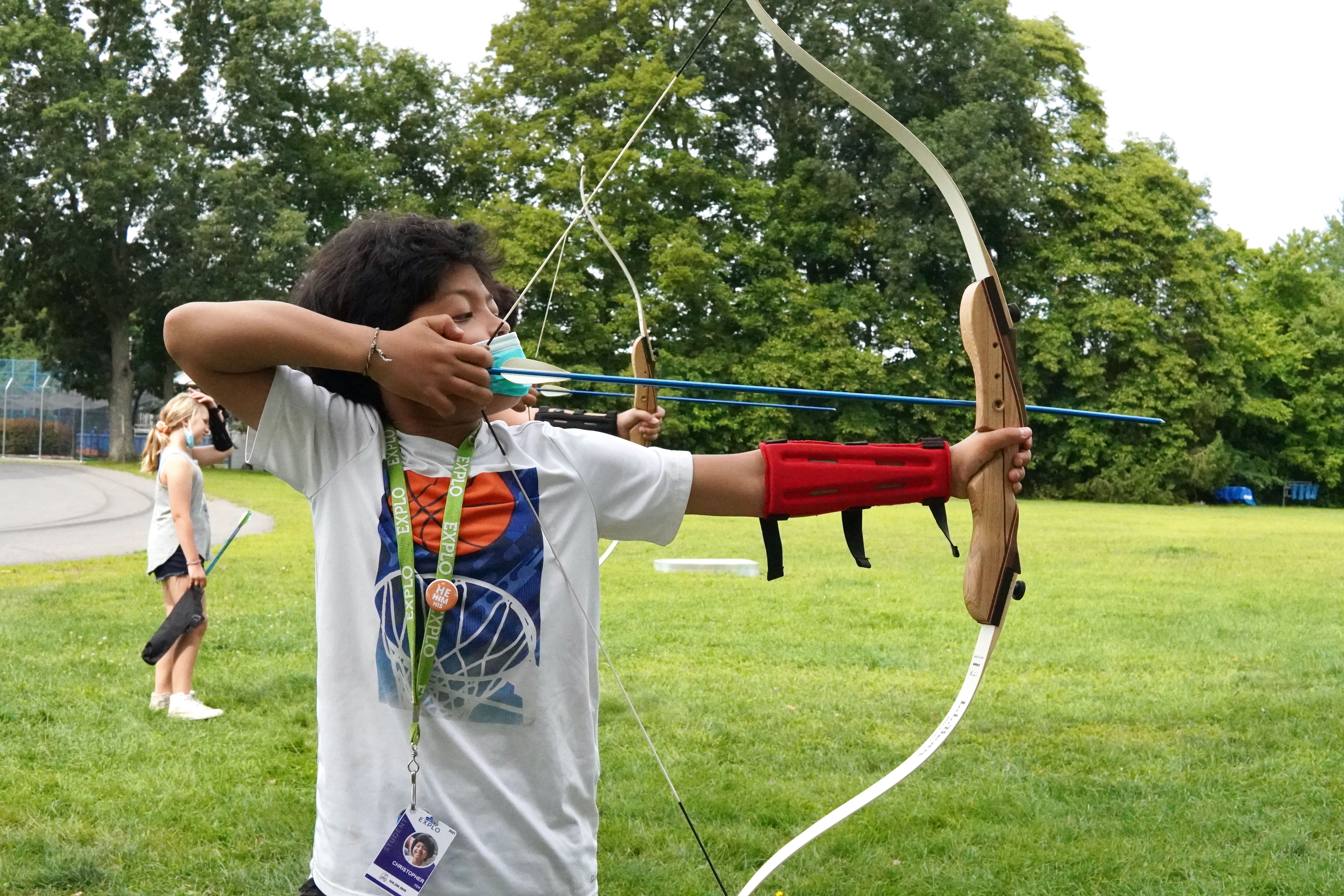 A student taking aim with a bow and arrow