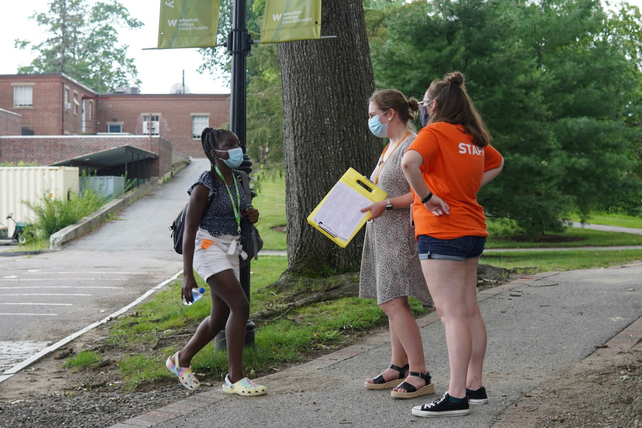 Two staff members greet a new EXPLO student