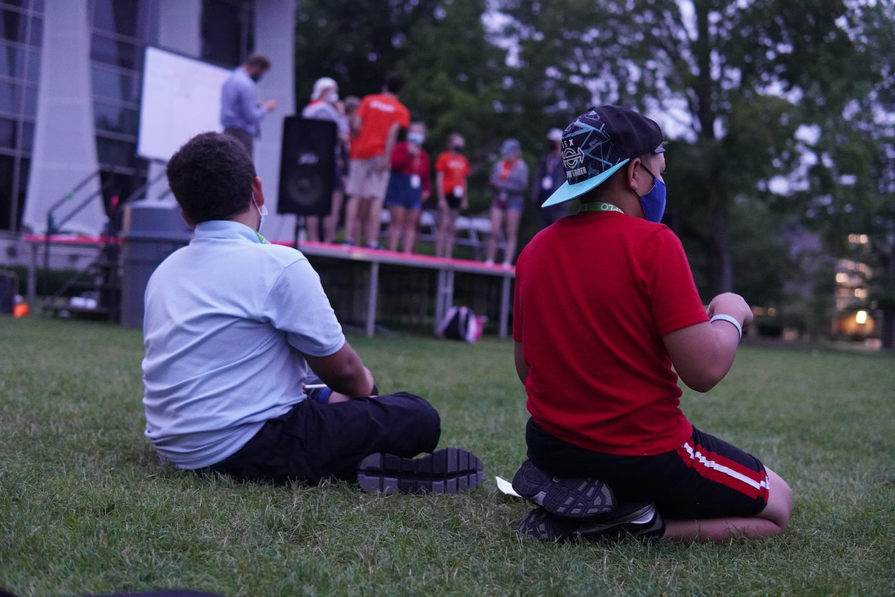 Two students watch as staff members perform a skit on the quad stage