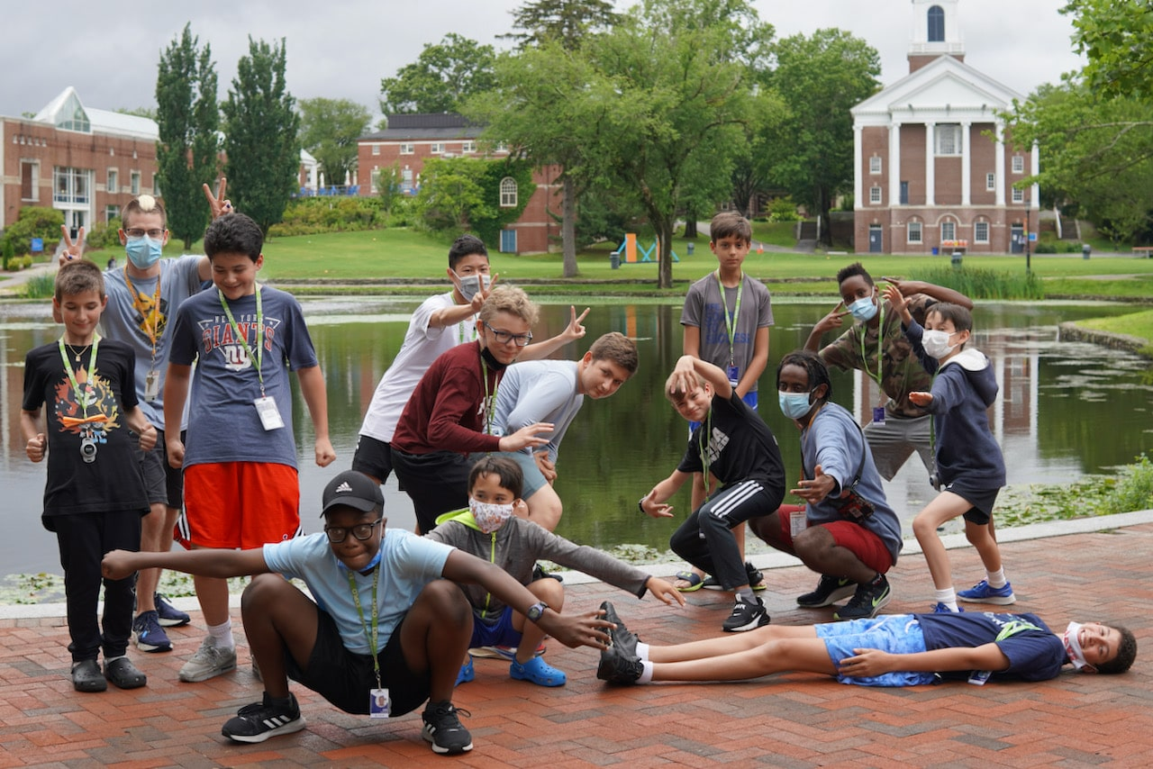 A living group poses in front of a backdrop of the Wheaton Campus