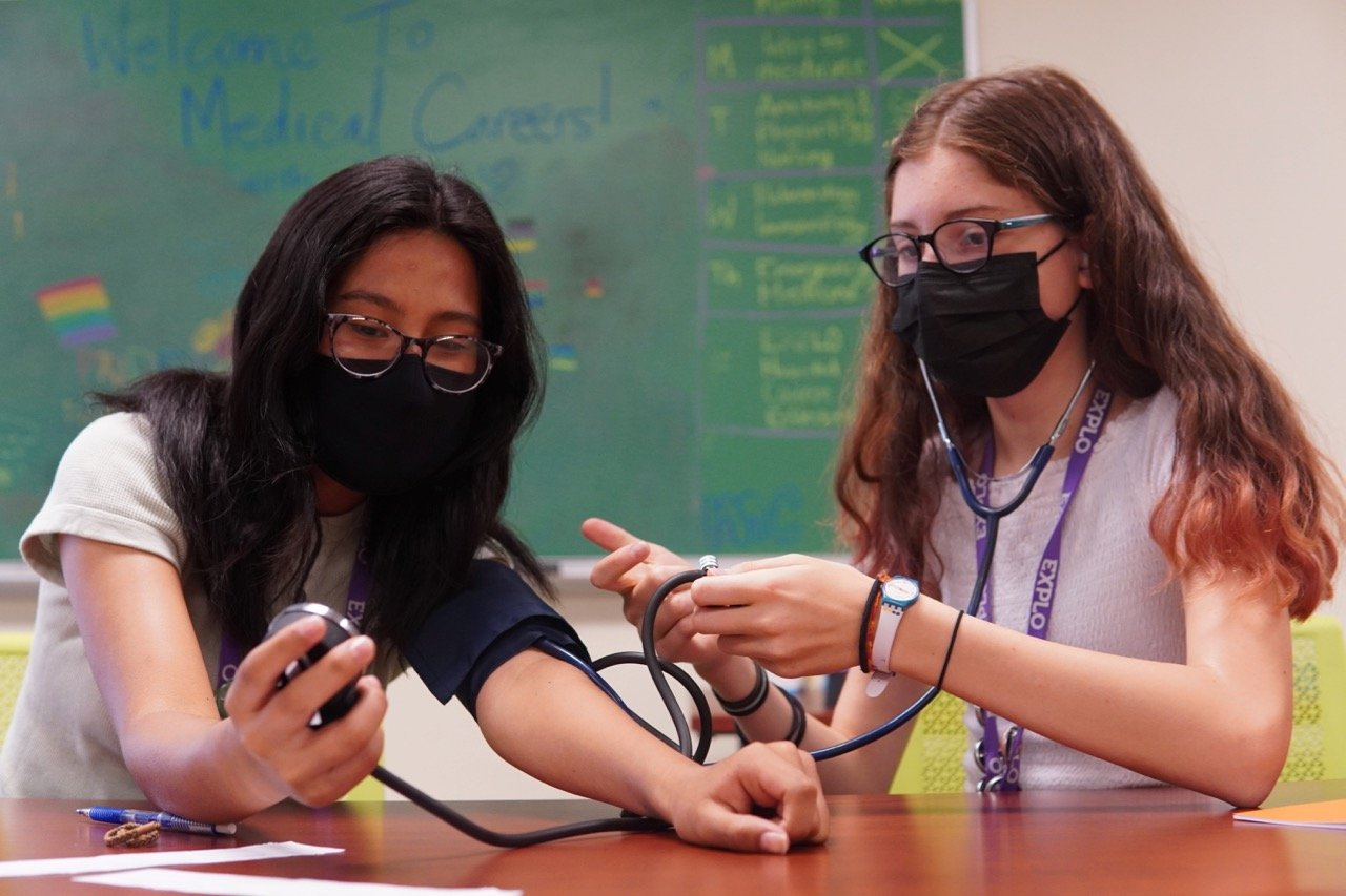 Two students wearing white shirts practice taking blood pressure together as a green chalkboard with