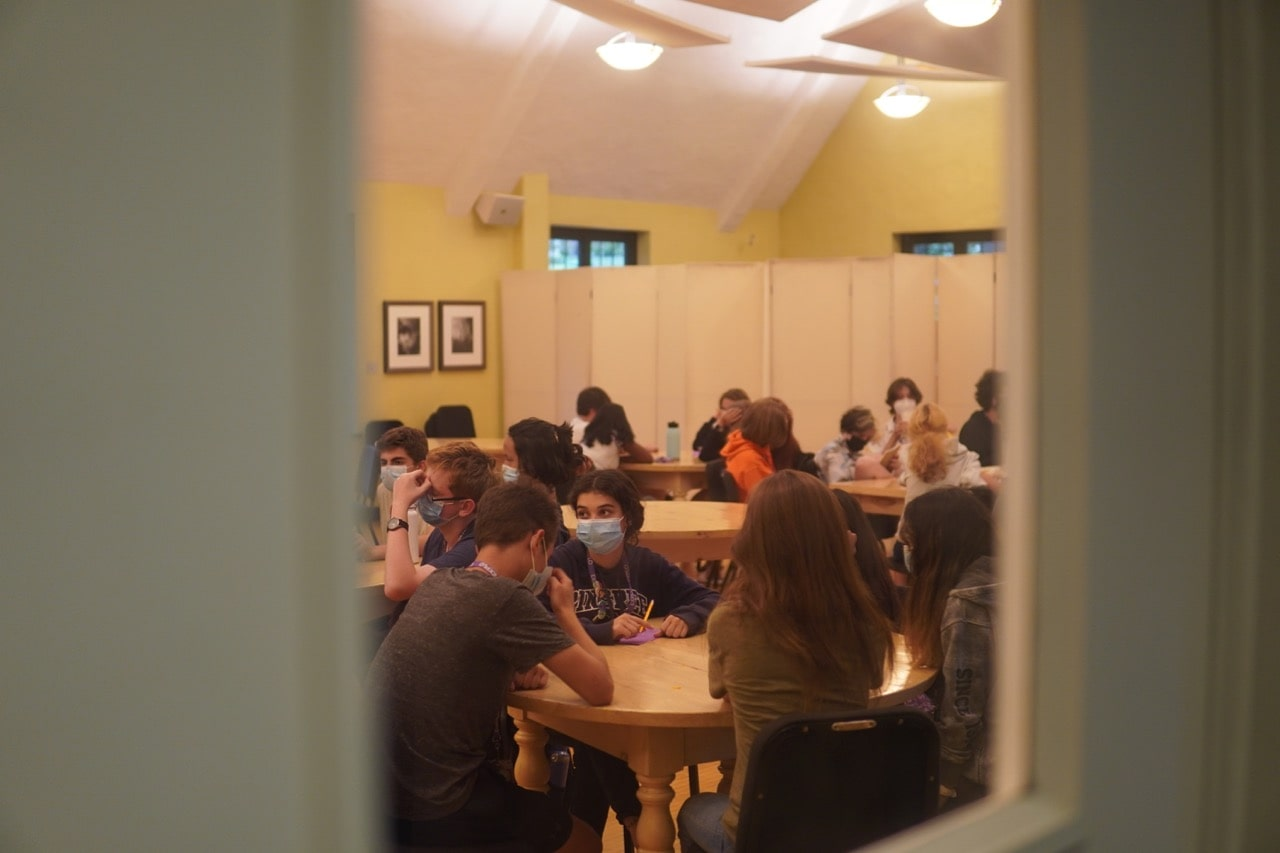 A view through the window on the door of the room of students sitting at round tables with their trivia teams