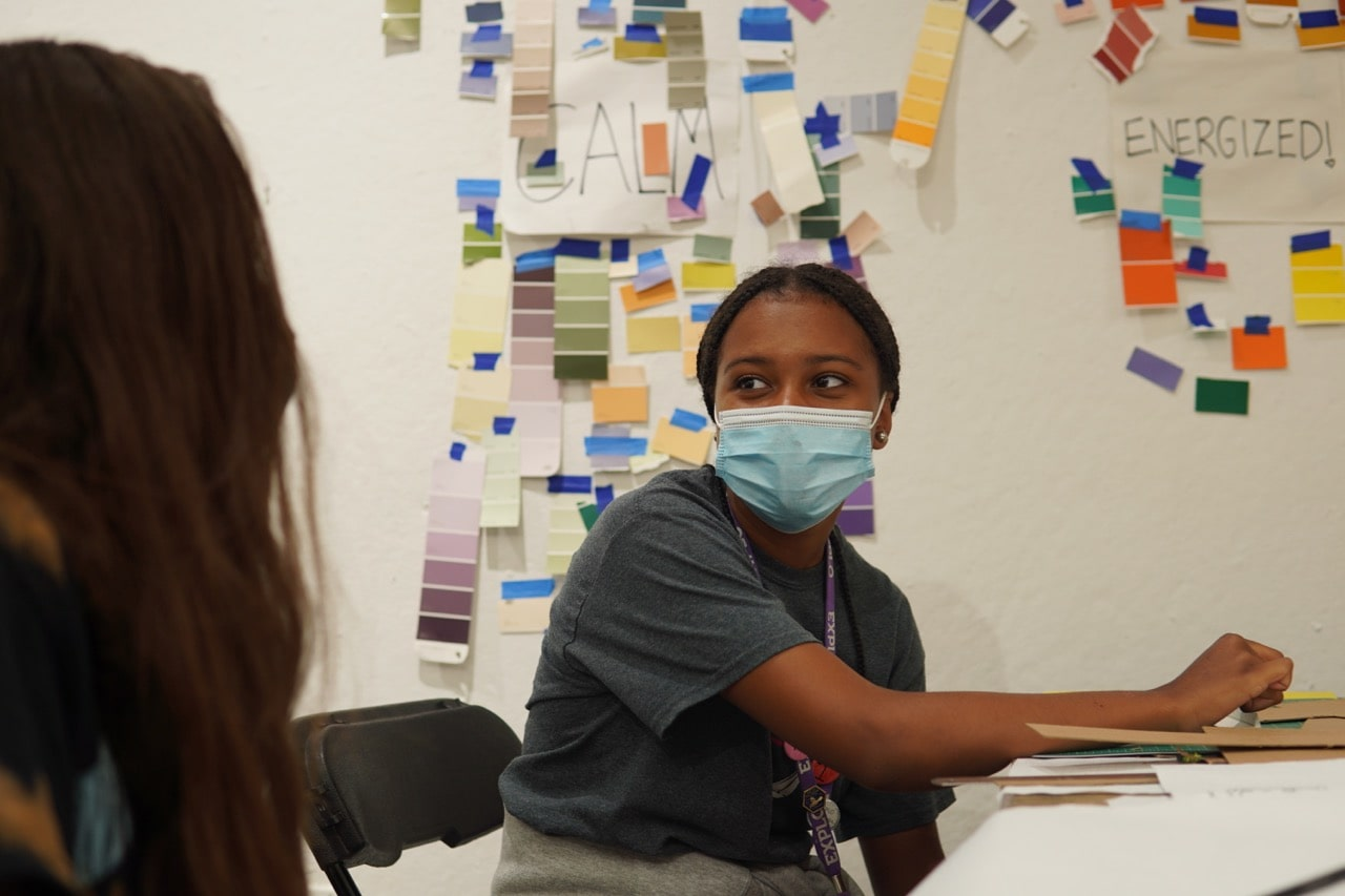 Student wearing navy shirt sits at desk speaking with another student as paint color samples are visible stuck on the wall in the background