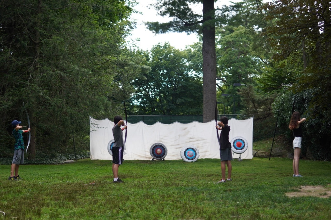 Four students stand ready to release their arrows and try to hit the balloons at the center of their targets as a white sheet and trees are seen in the background