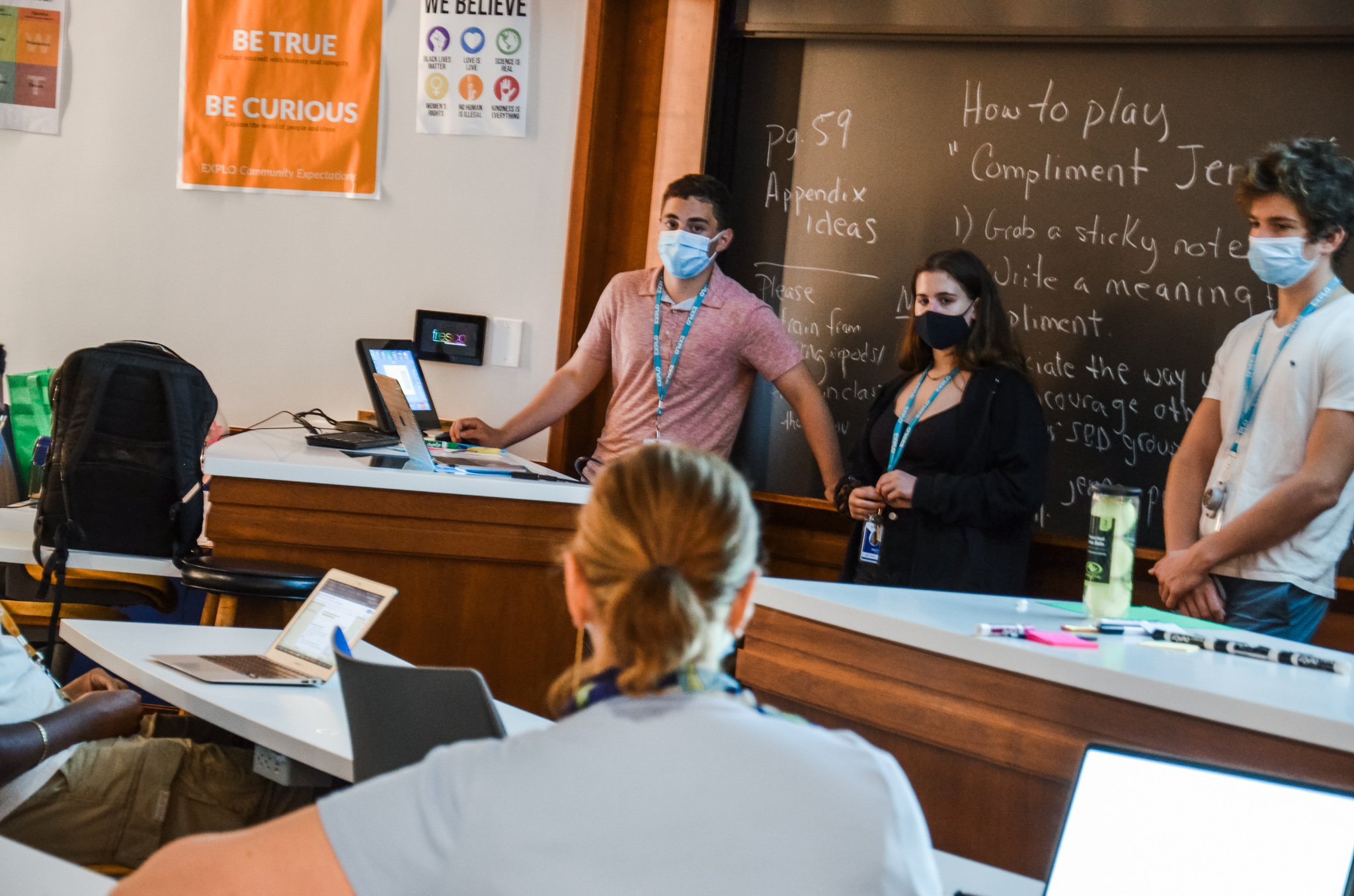 Three students stand in front of a blackboard while other students watch intently