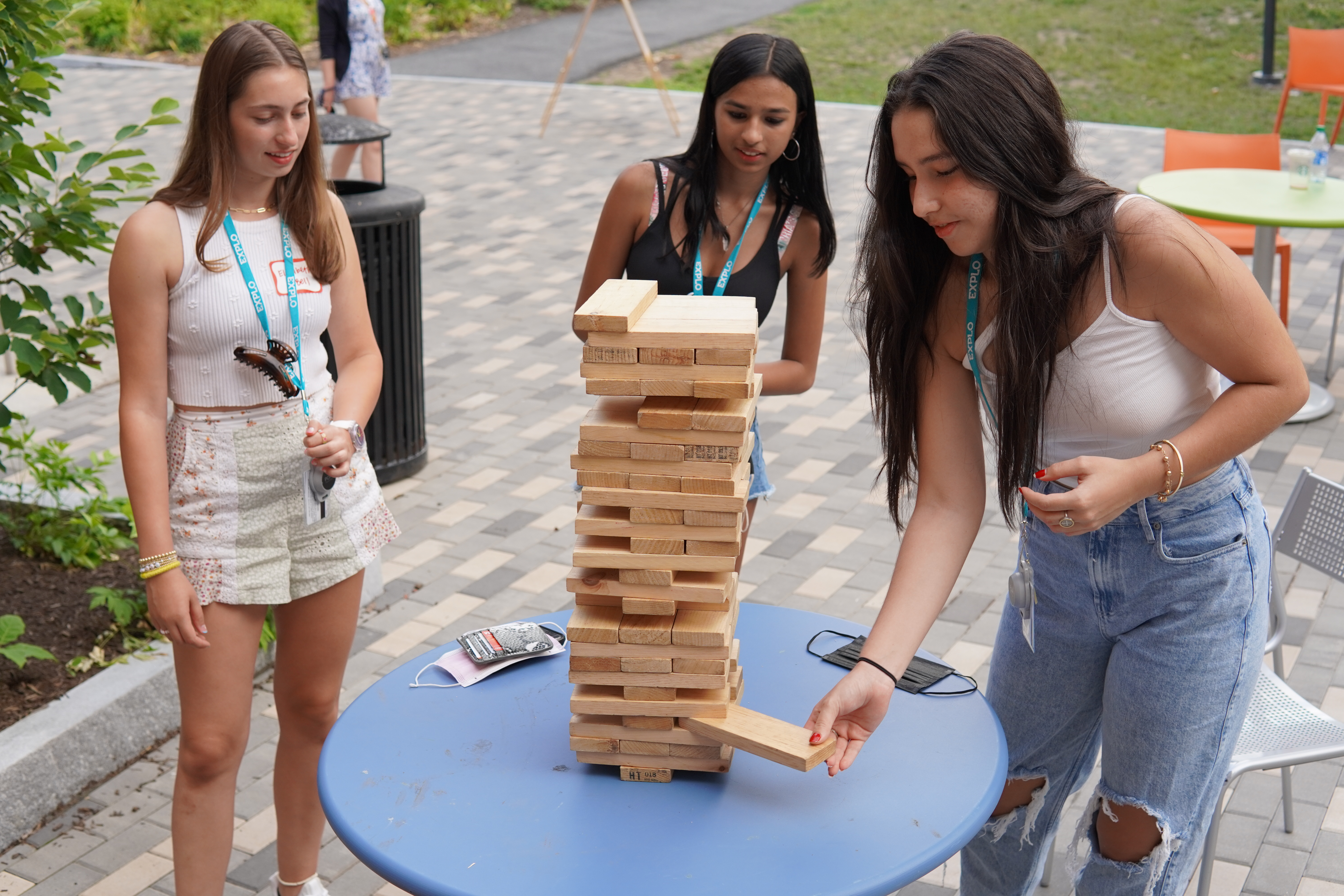 A student pulls a block from near the base of the tower as two others look on in hopes that it falls for their competitor