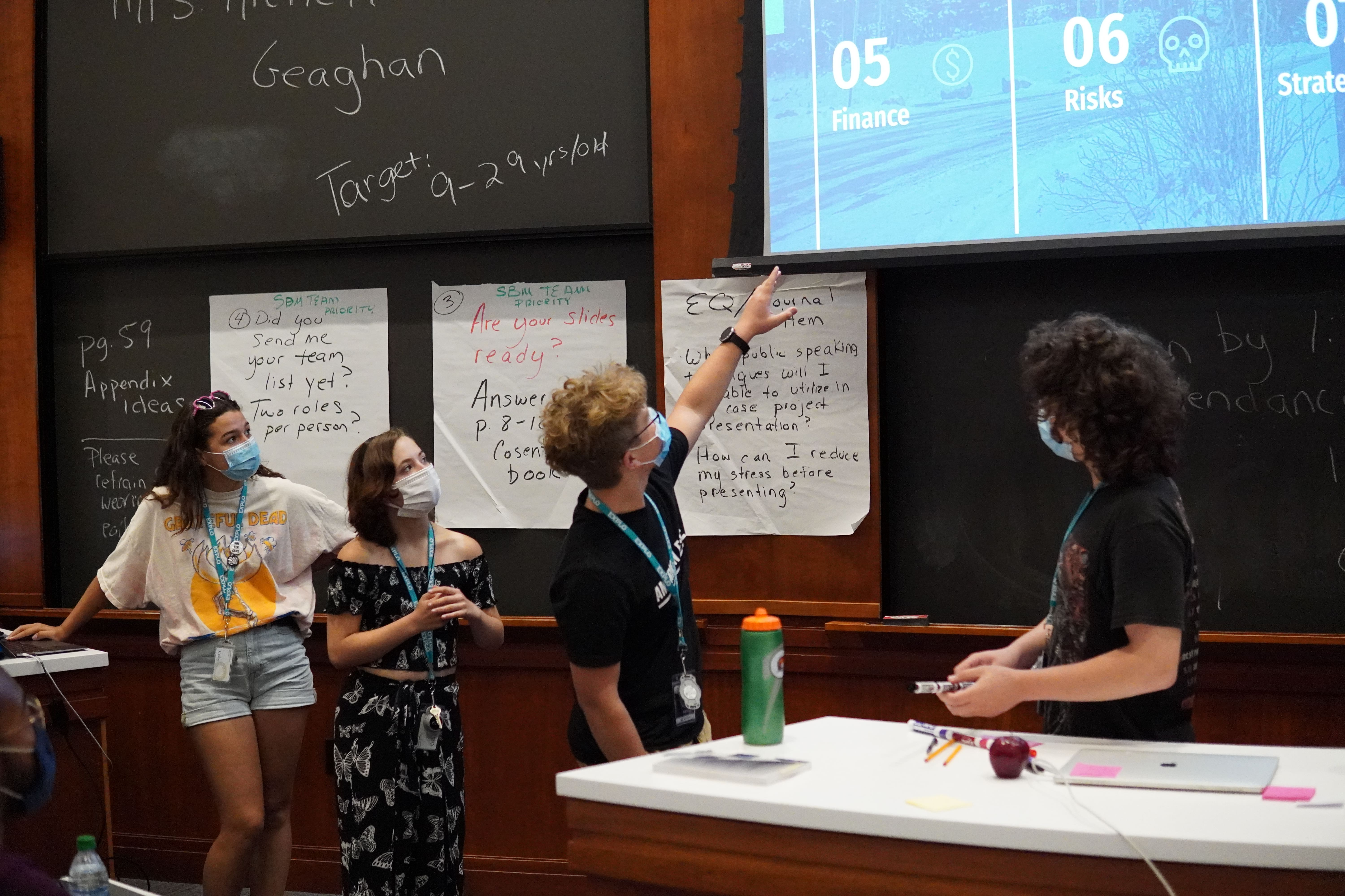 Four students stand below a projector screen as they present. One gestures upward toward their presentation, while the others listen.