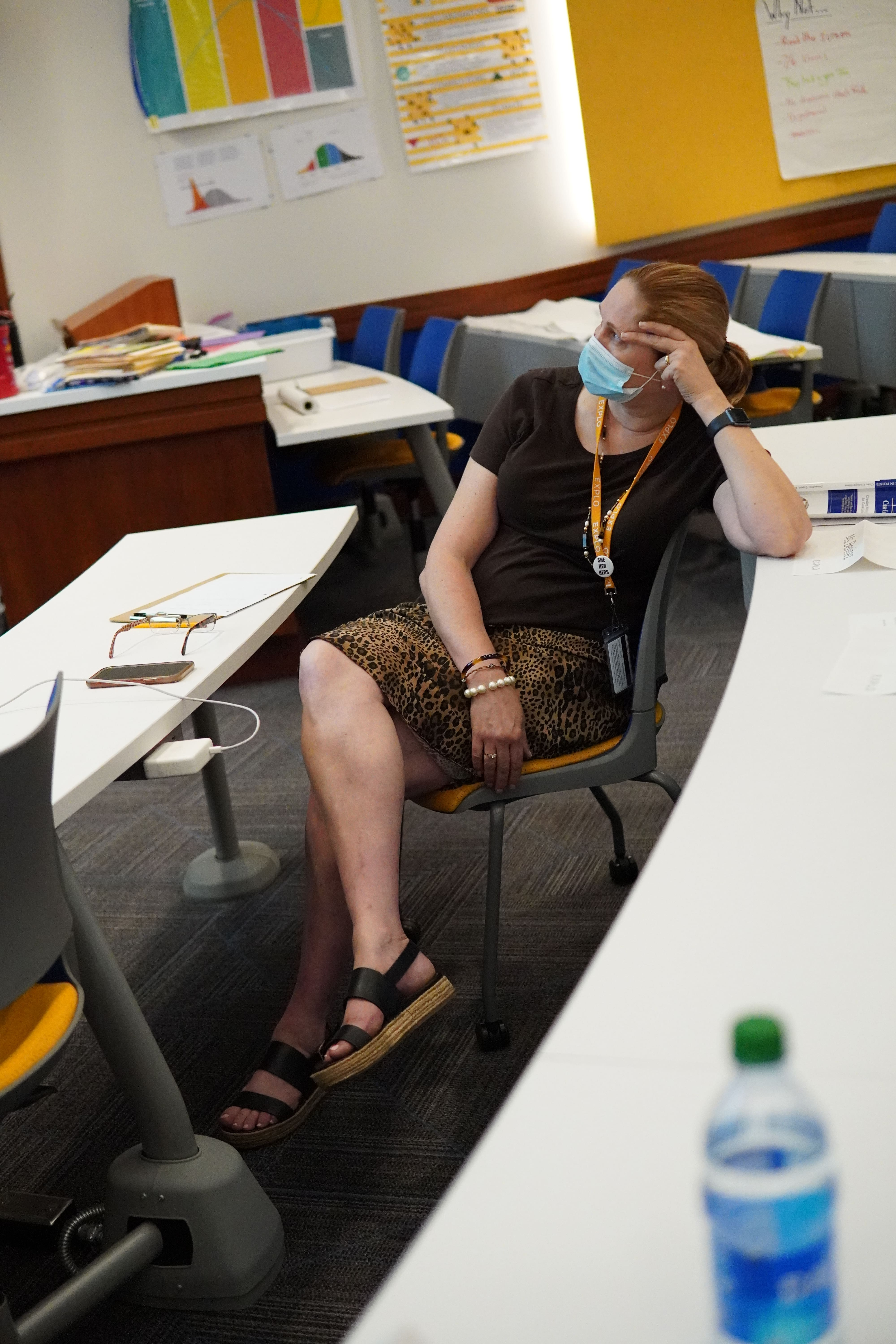 Instructor Barbara Bernier leans back in her chair as she listens to the first practice presentation of the day.