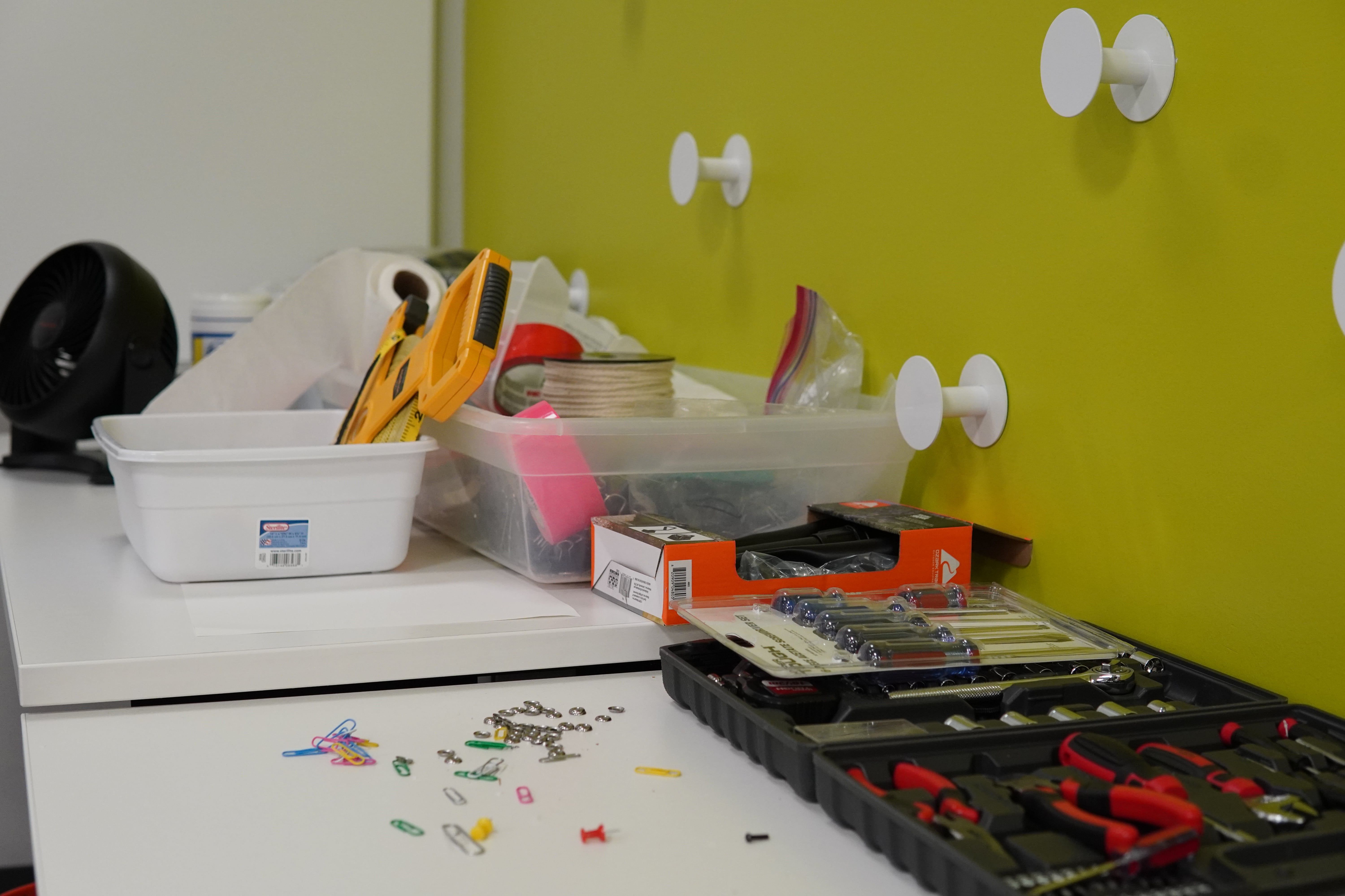 Various tools and supplies are opened on a table in front of a green wall.