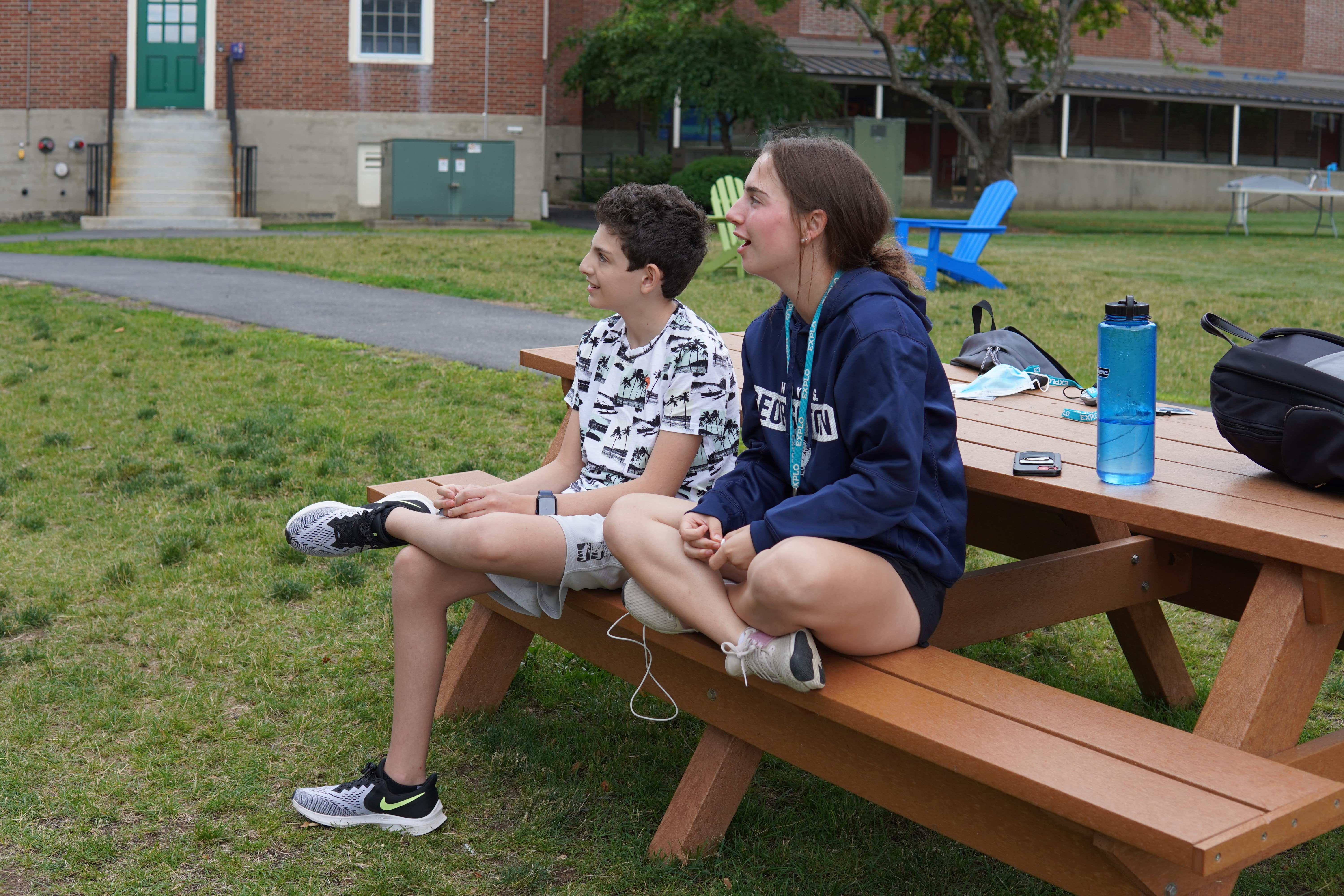 Two students sit on a picnic table bench. There is a water bottle, backpack, and other items on the table.