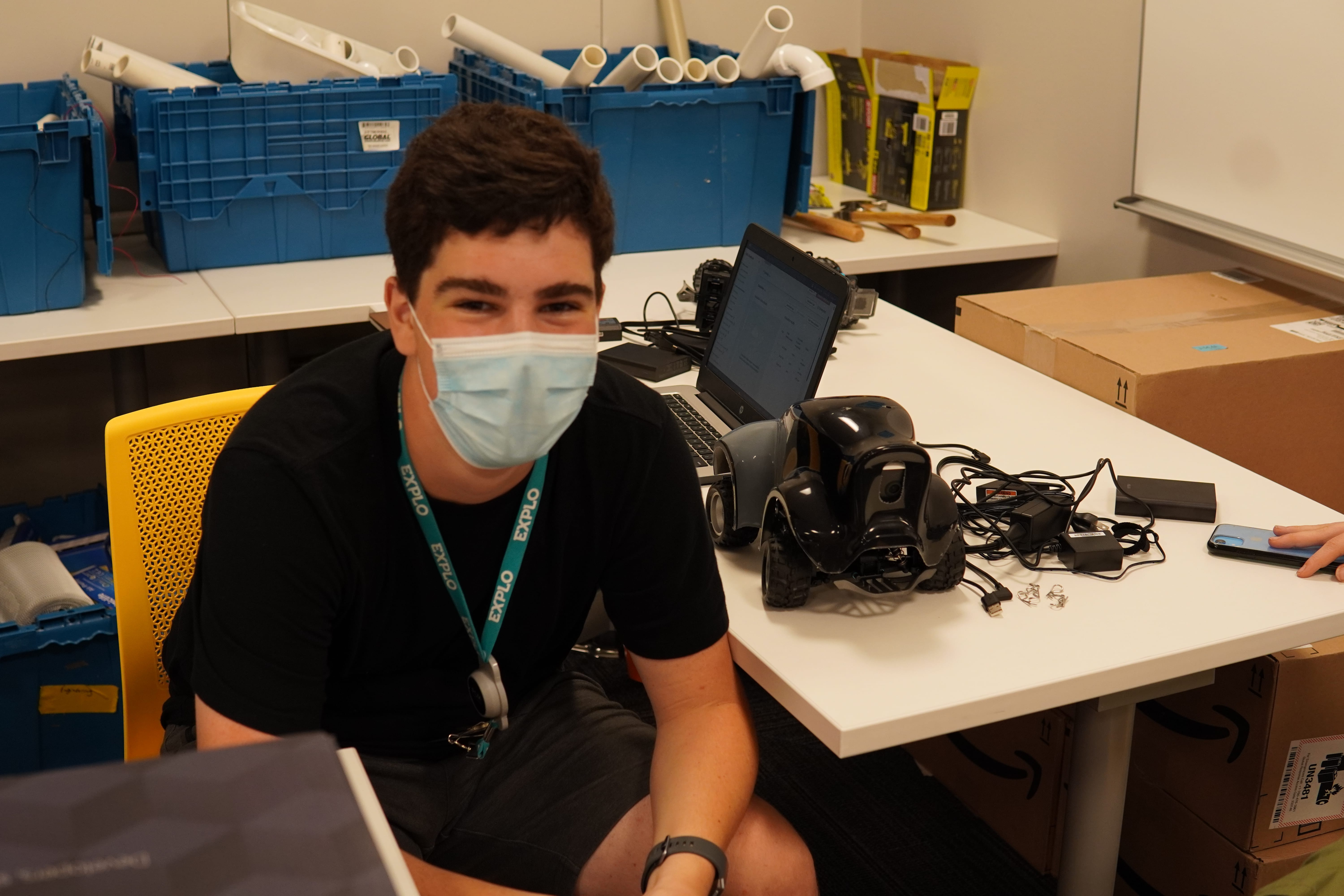 A student smiles under their mask as they sit next to their deconstructed car and computer