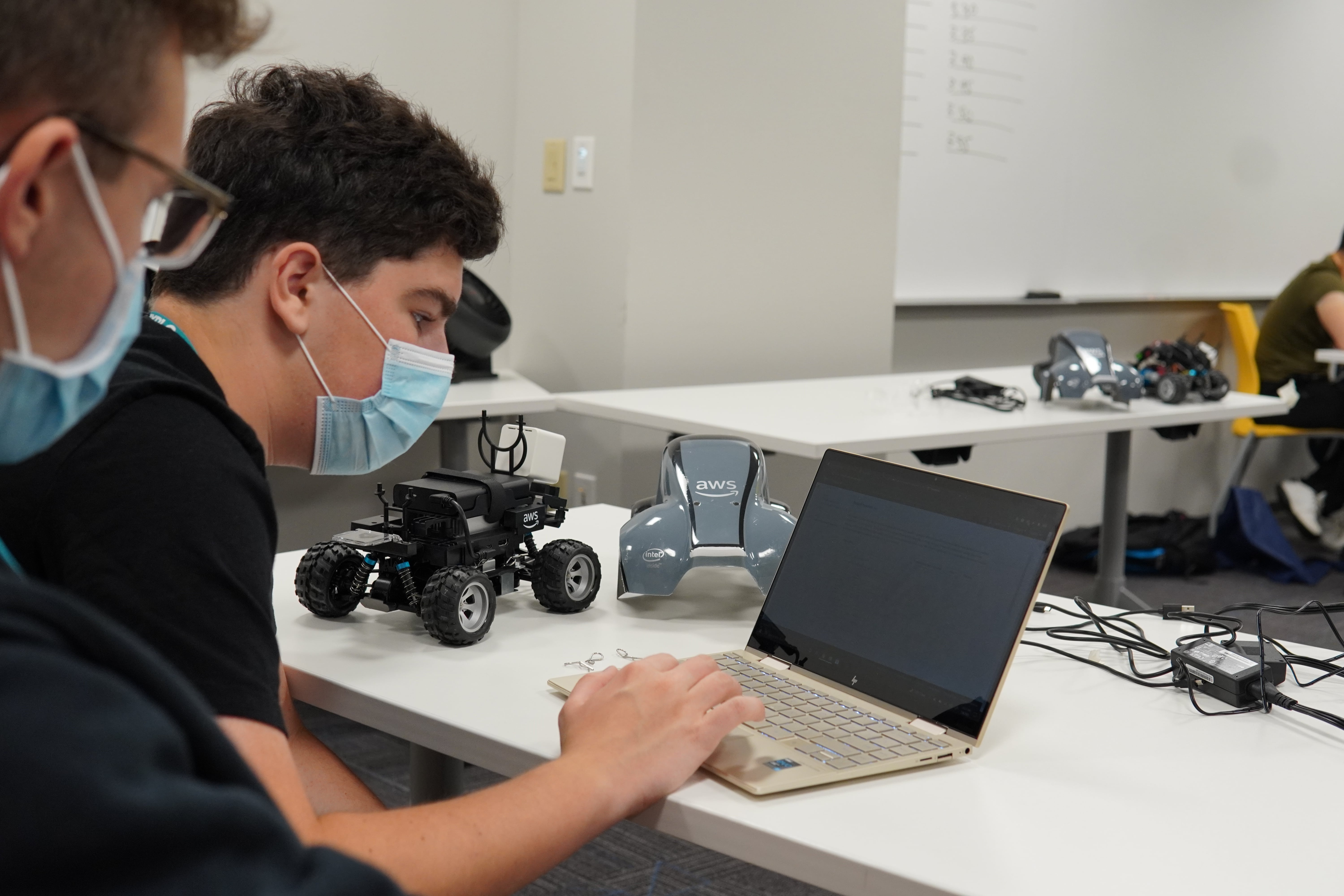 Two students lean in to check the data from their test run on their computer. Their self driving car is deconstructed on the table next to them.