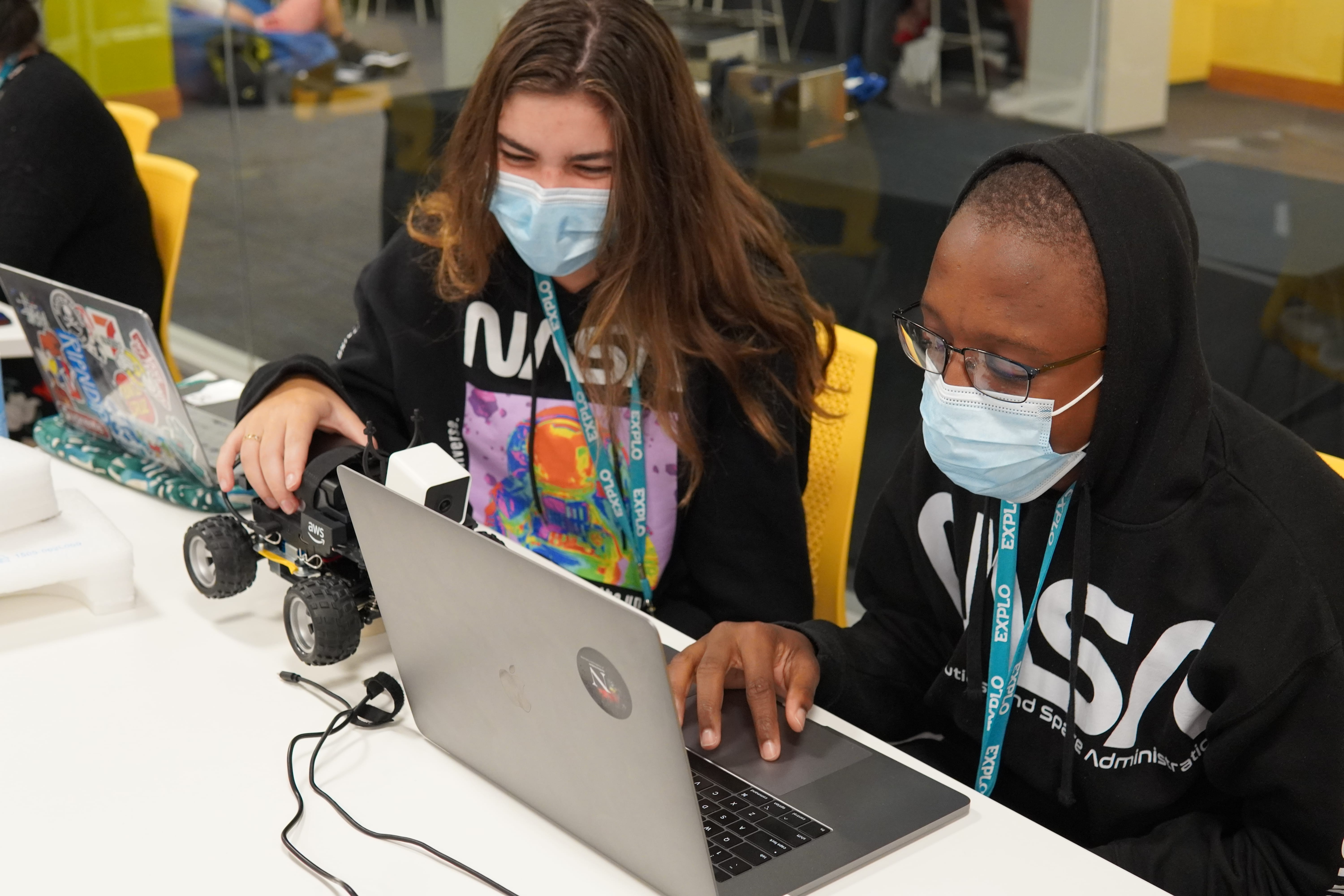 Two students work at a computer as they work through the errors in the programming of their self driving cars. One student holds the car while the other has their finger on the trackpad.