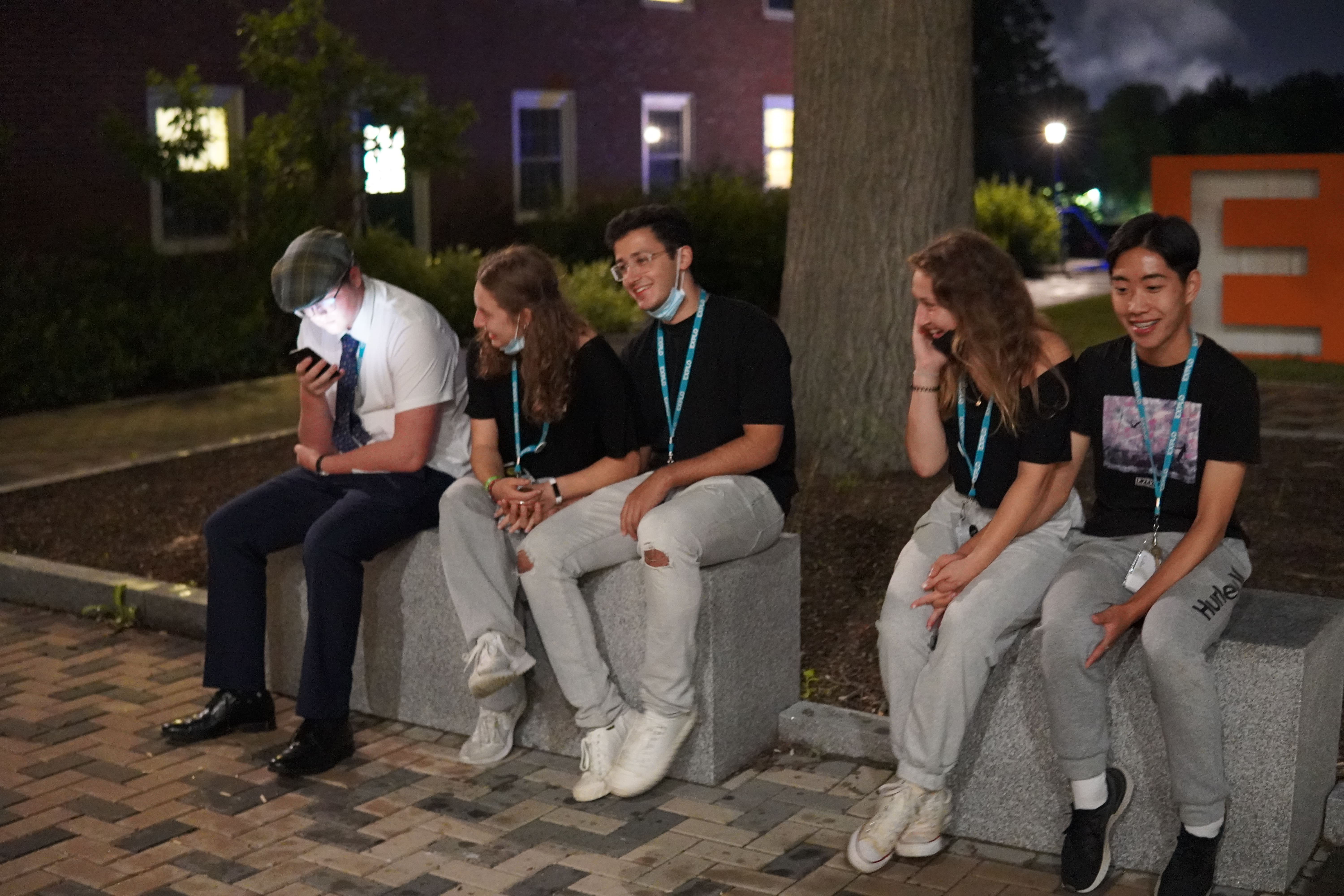 Five students sit on stone blocks outside. Two couples are holding hands and the fifth person is on their phone.