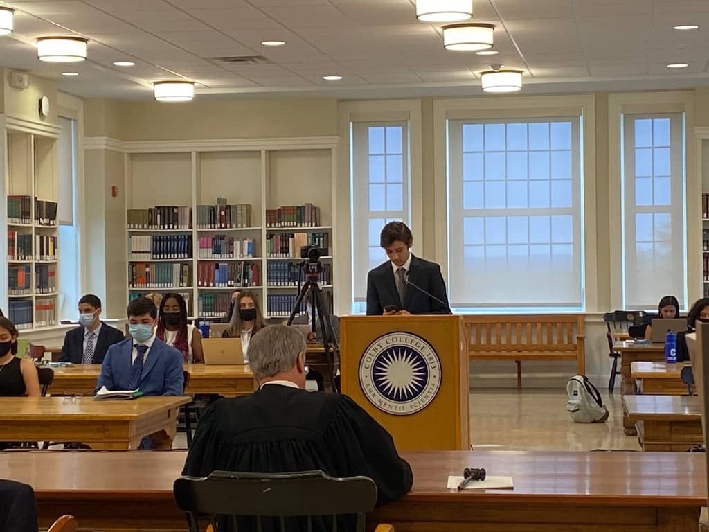 A male student with brown hair stands at a podium delivering remarks to a judge seated in front of him