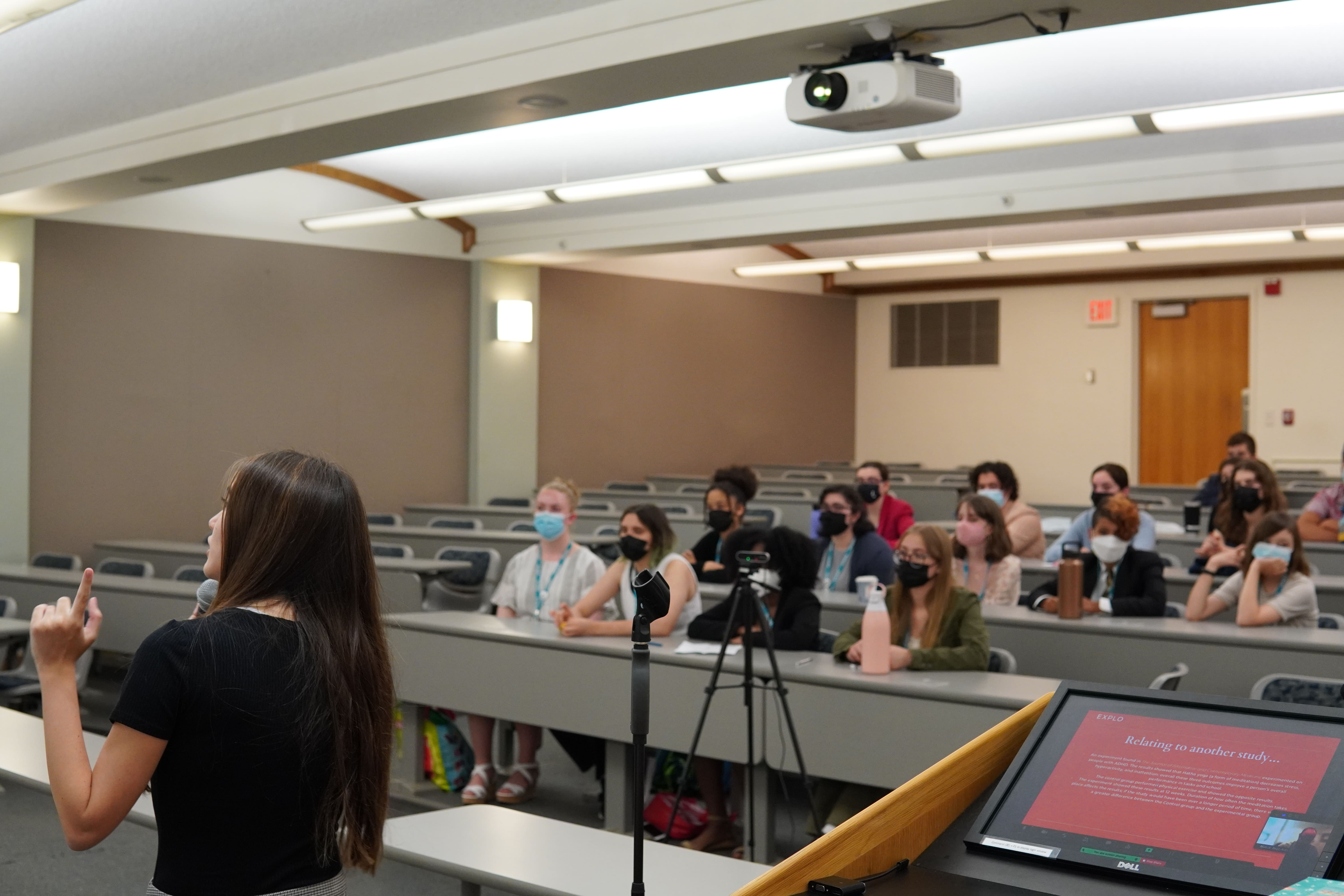 The student gestures toward information behind them as they present to their peers and instructors in front of them, and experts watching through video.