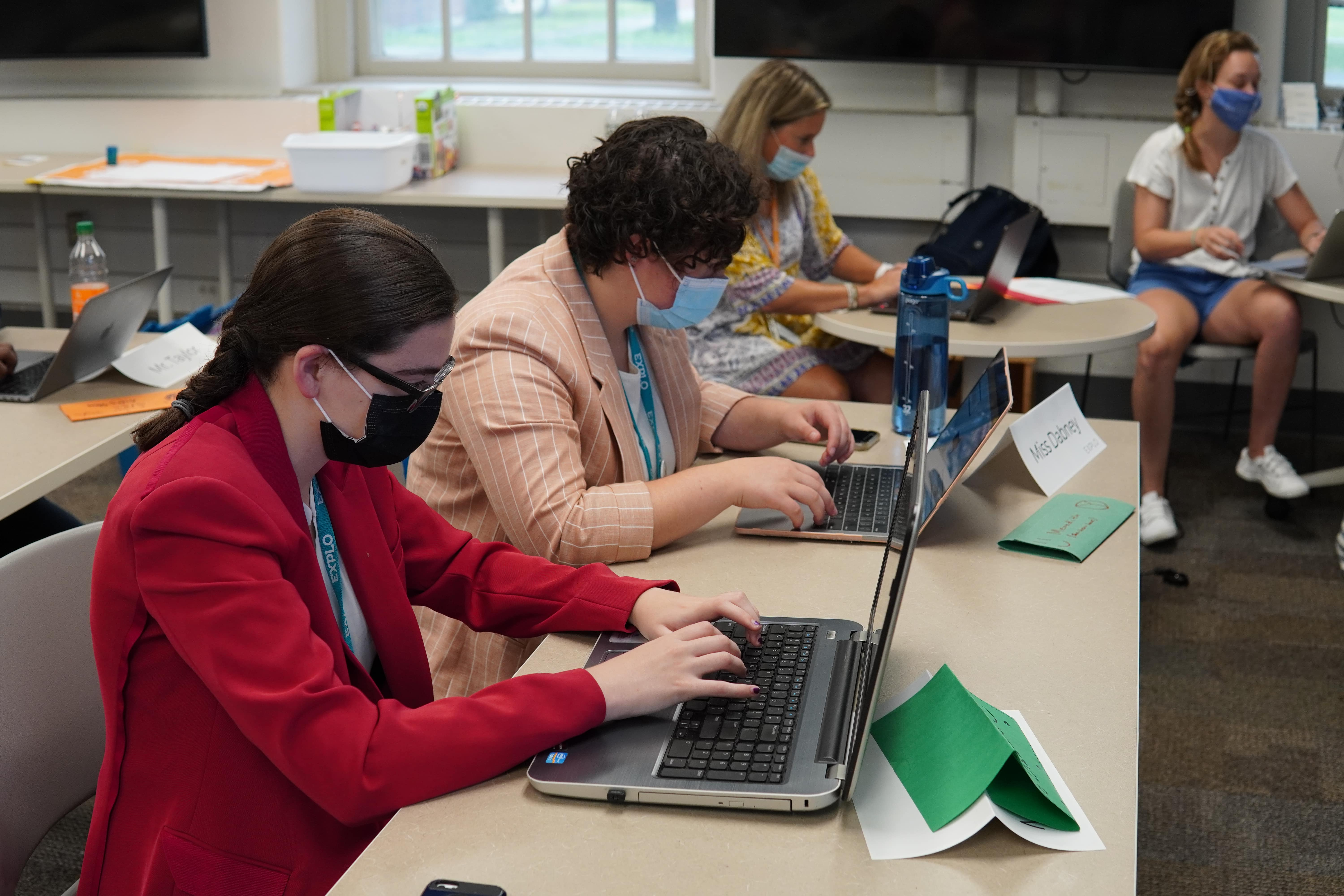 Students work at their laptops in the classroom as their instructors complete their own preparations behind them.