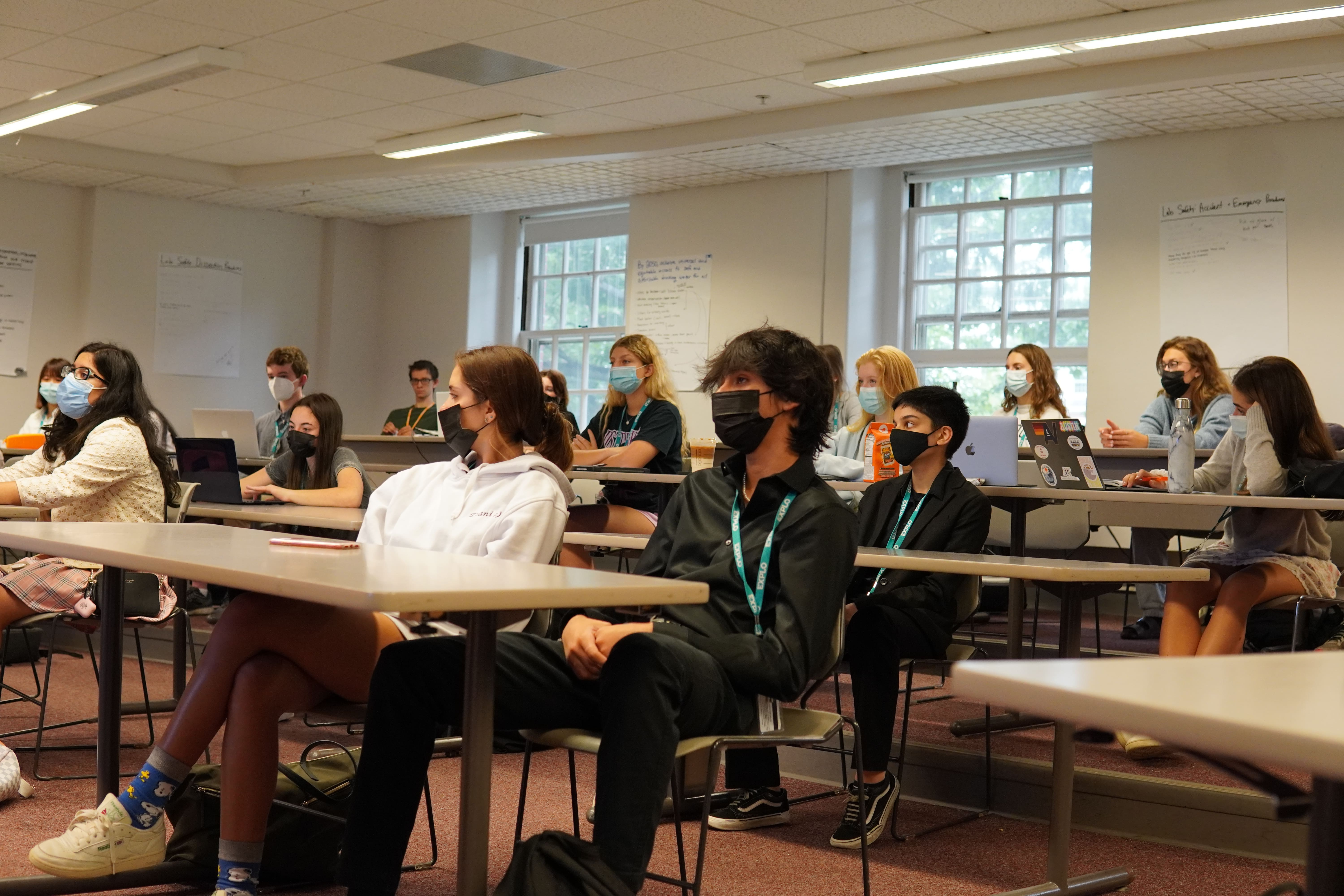 Rows of students listen in a classroom to a discussion on medical ethics.