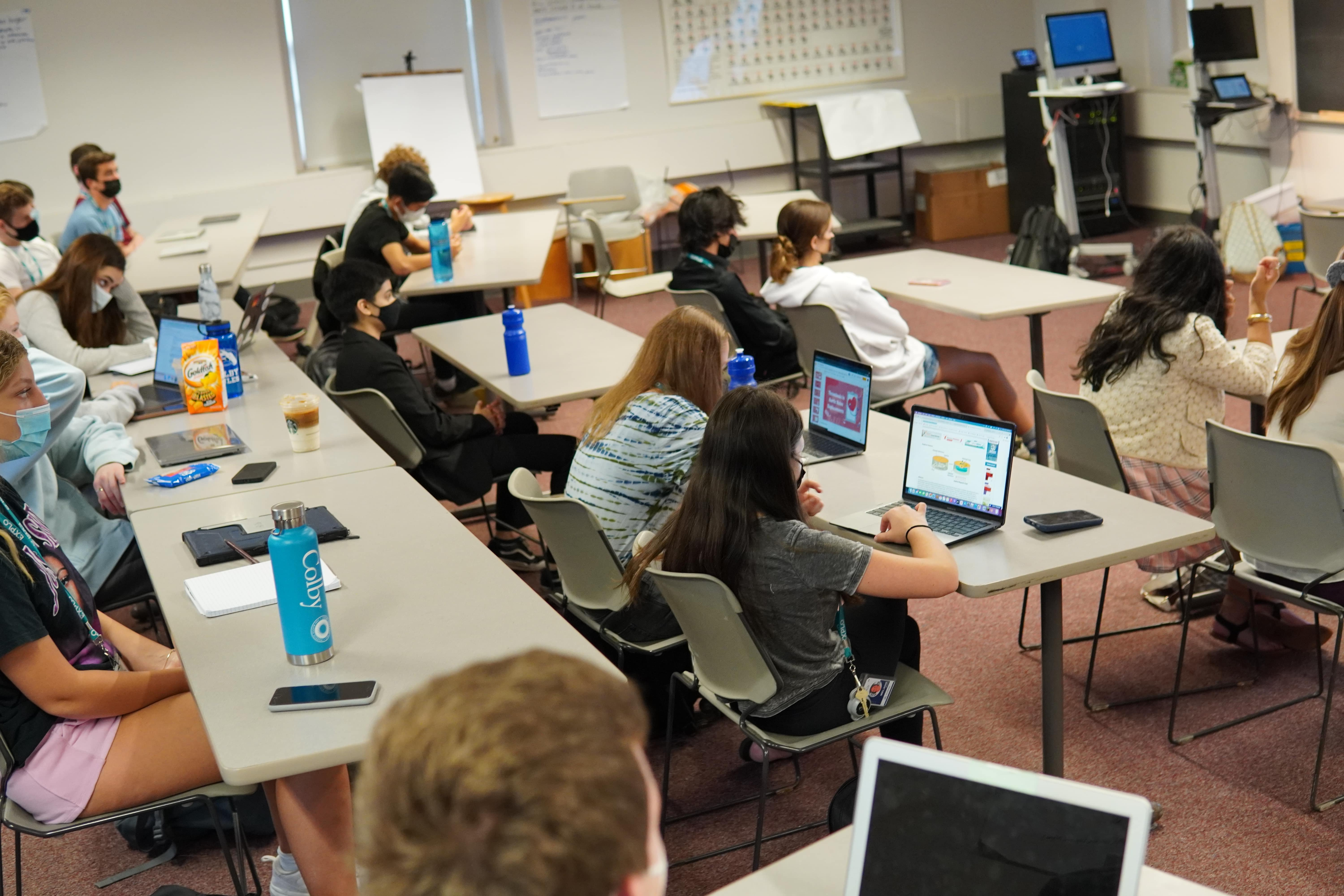 Students sit with their laptops and notebooks in front of them as they attend a morning discussion on medical ethics.