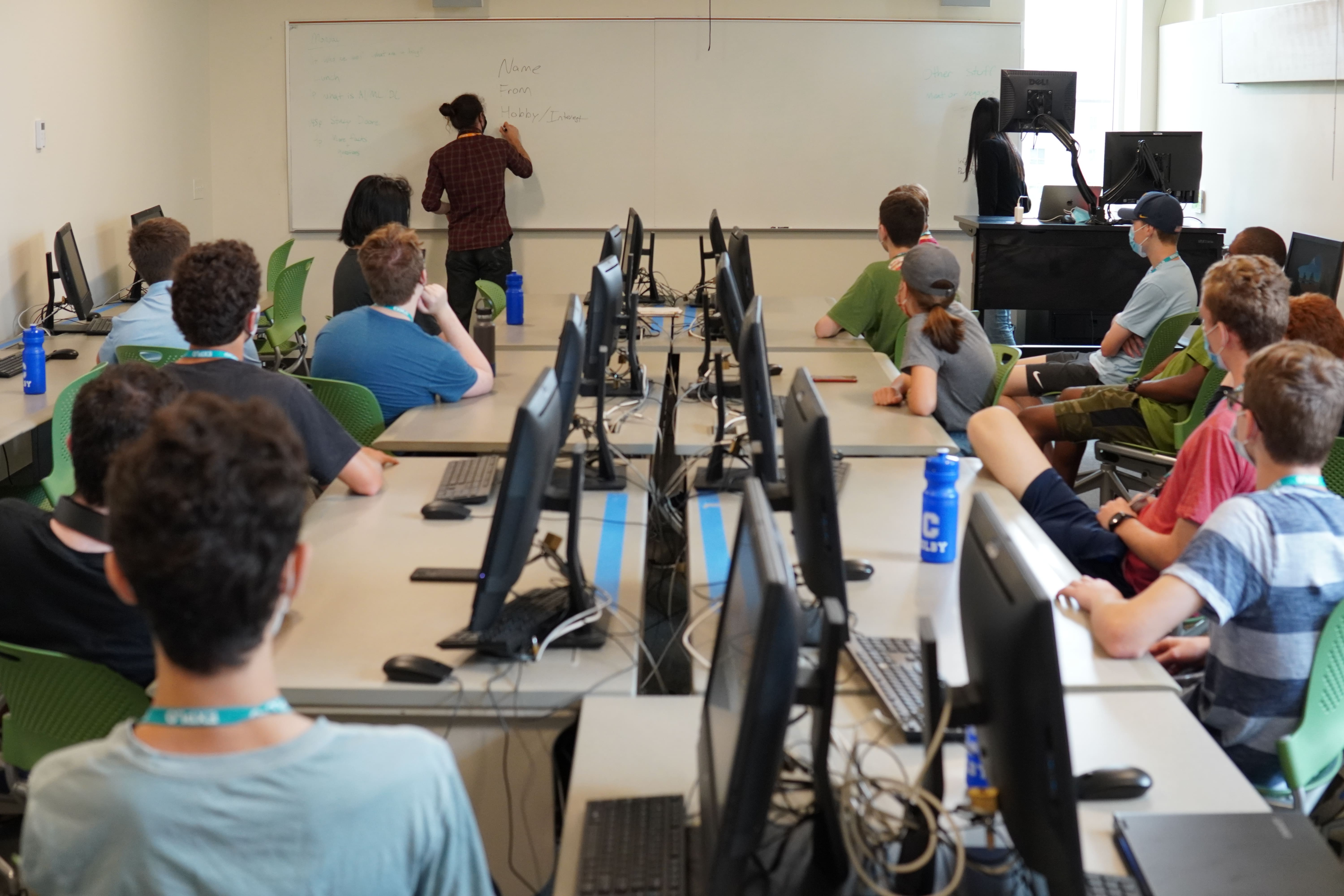 Students gathering in the computer lab for the first time watch as their teaching fellow write the instructions for their ice breaker on the board.