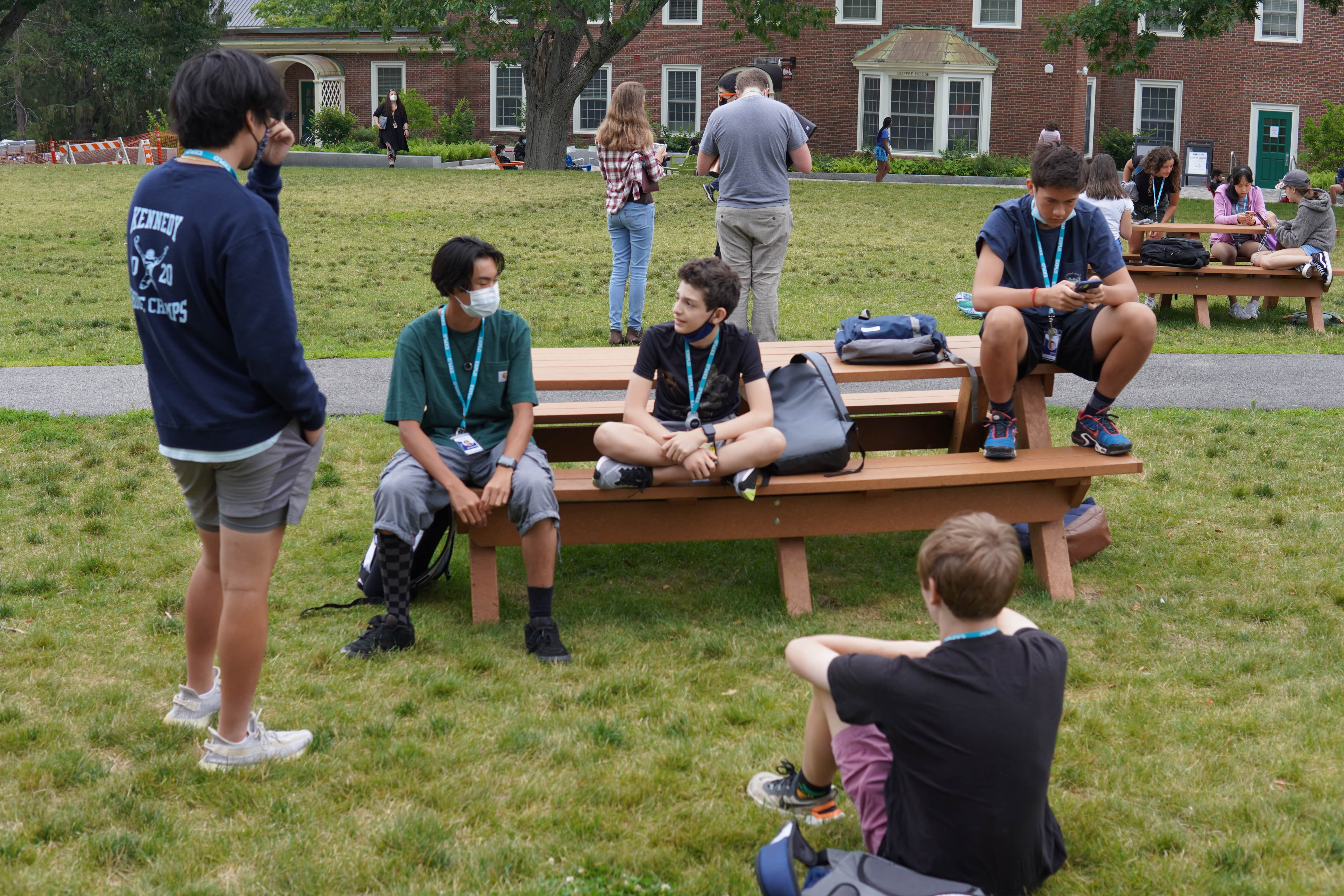 Students in at and around a picnic table with their bags close by as they wait for the morning meeting.