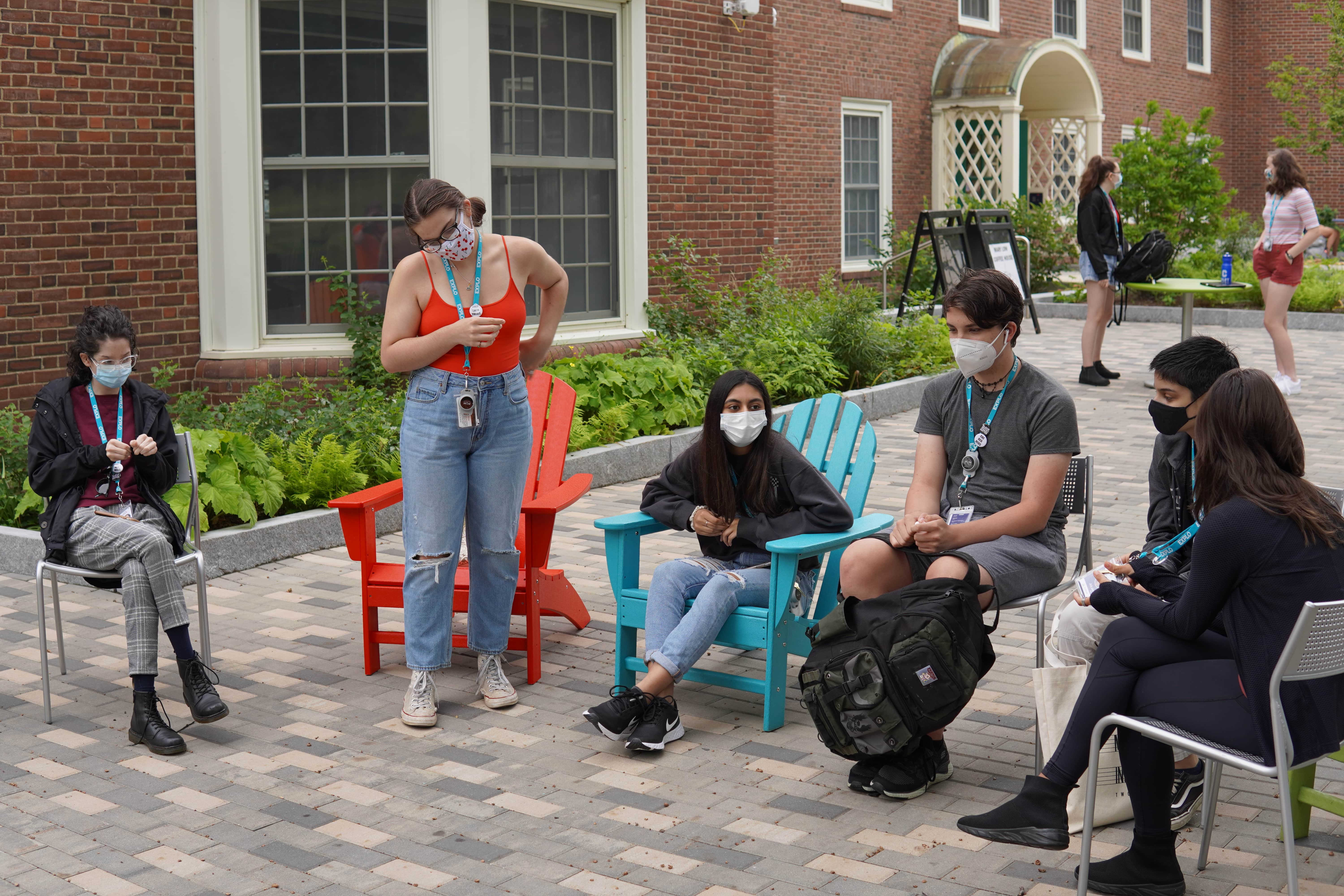 Students sit in a row of chairs along a bricked pathway, discussing their expectations for the concentration they're all enrolled in.