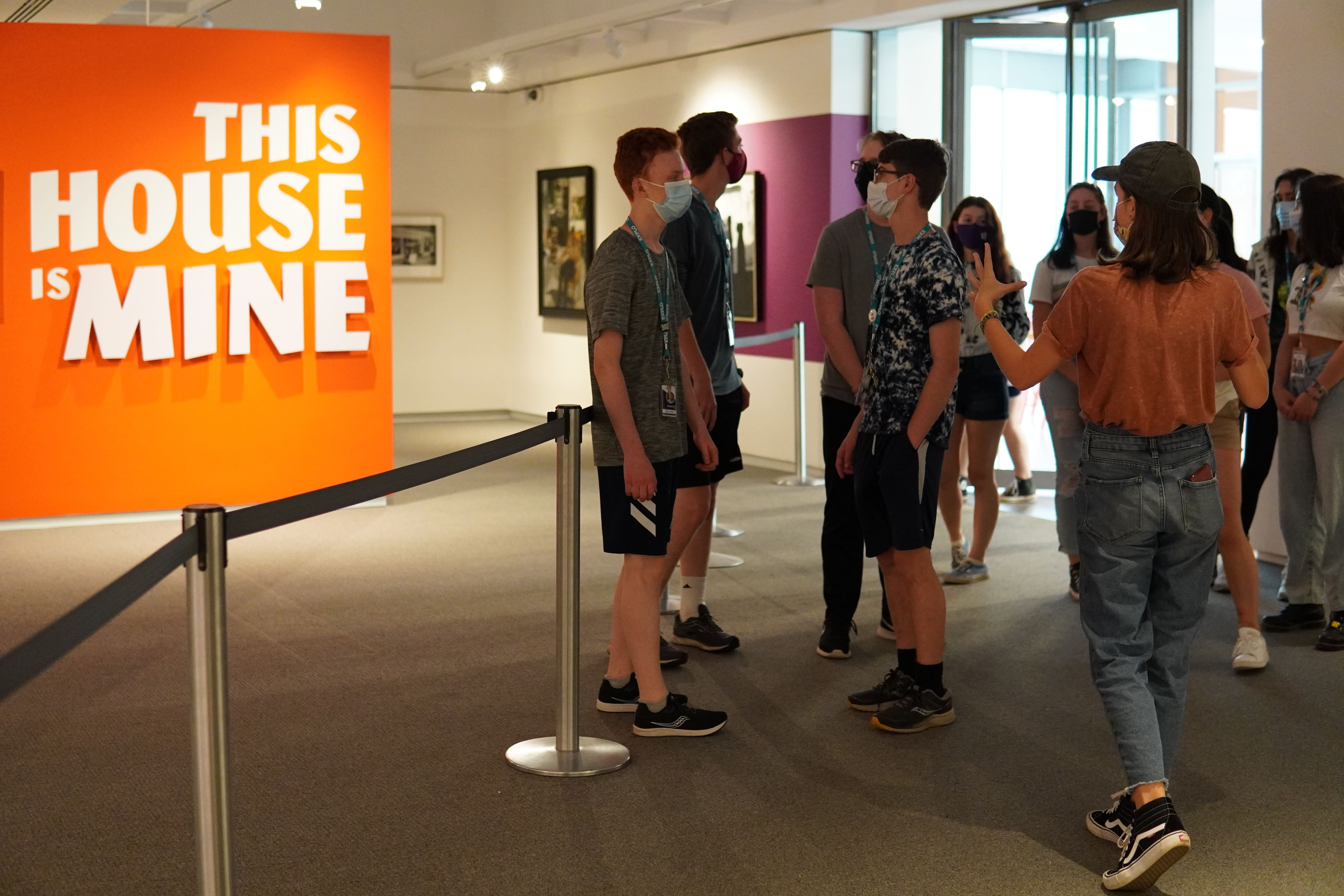 Students gather in the museum next to an exhibit titled