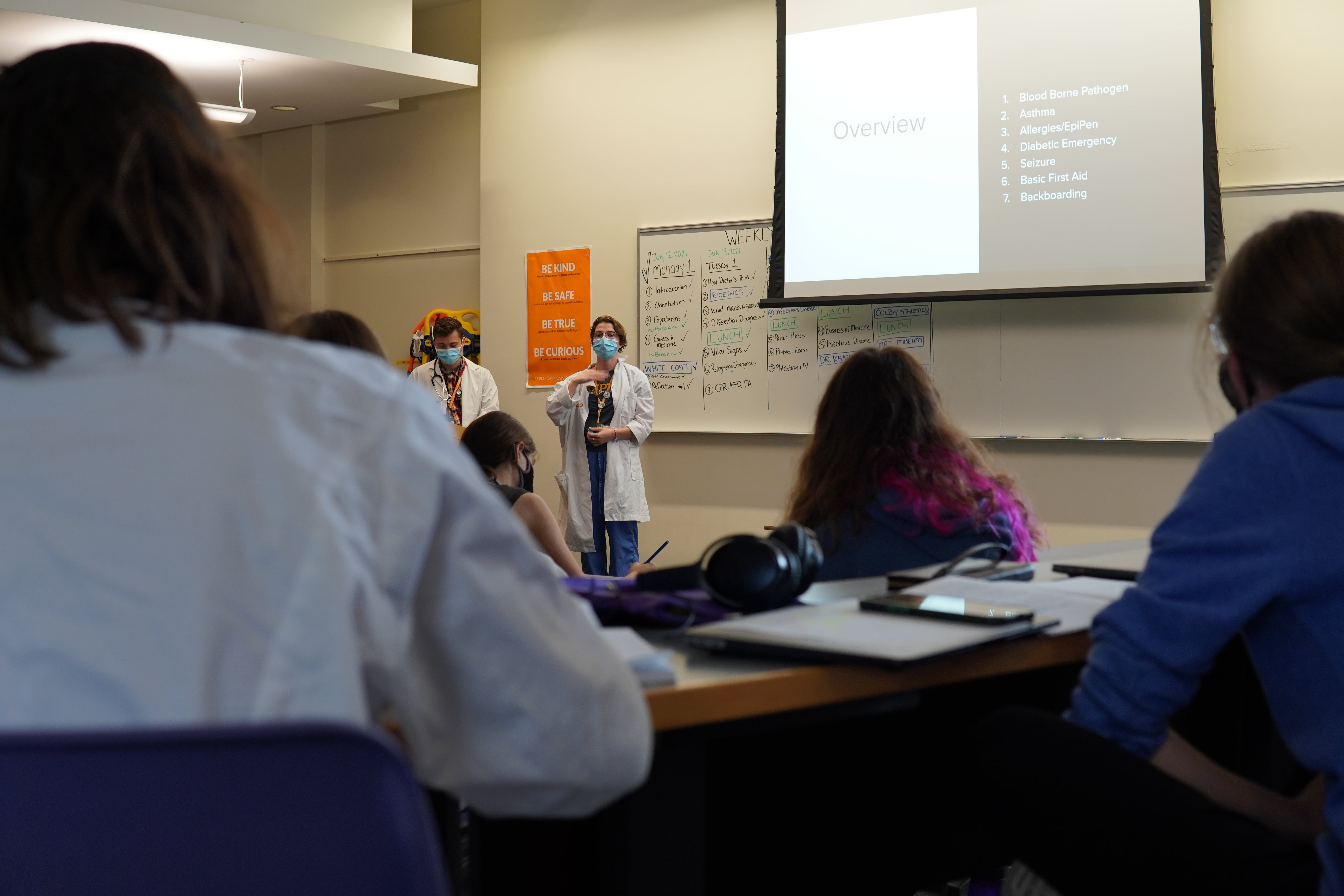 Teaching fellow and Instructor stand at the front of a lecture hall as students listen to their presentation.