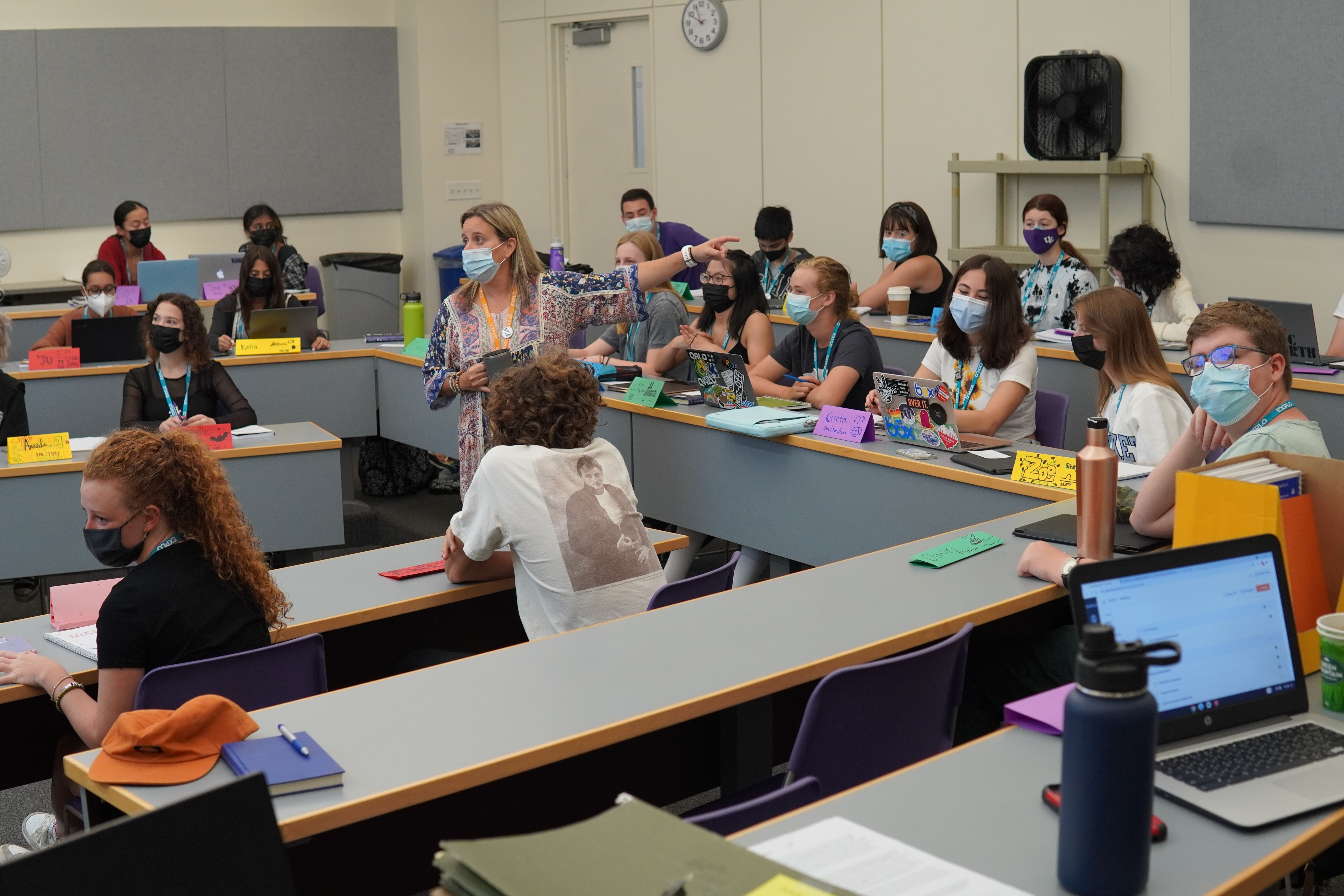 Students in the Psychology Concentration listen as their Instructor answers a question for a student while she wanders between the rows of desks.