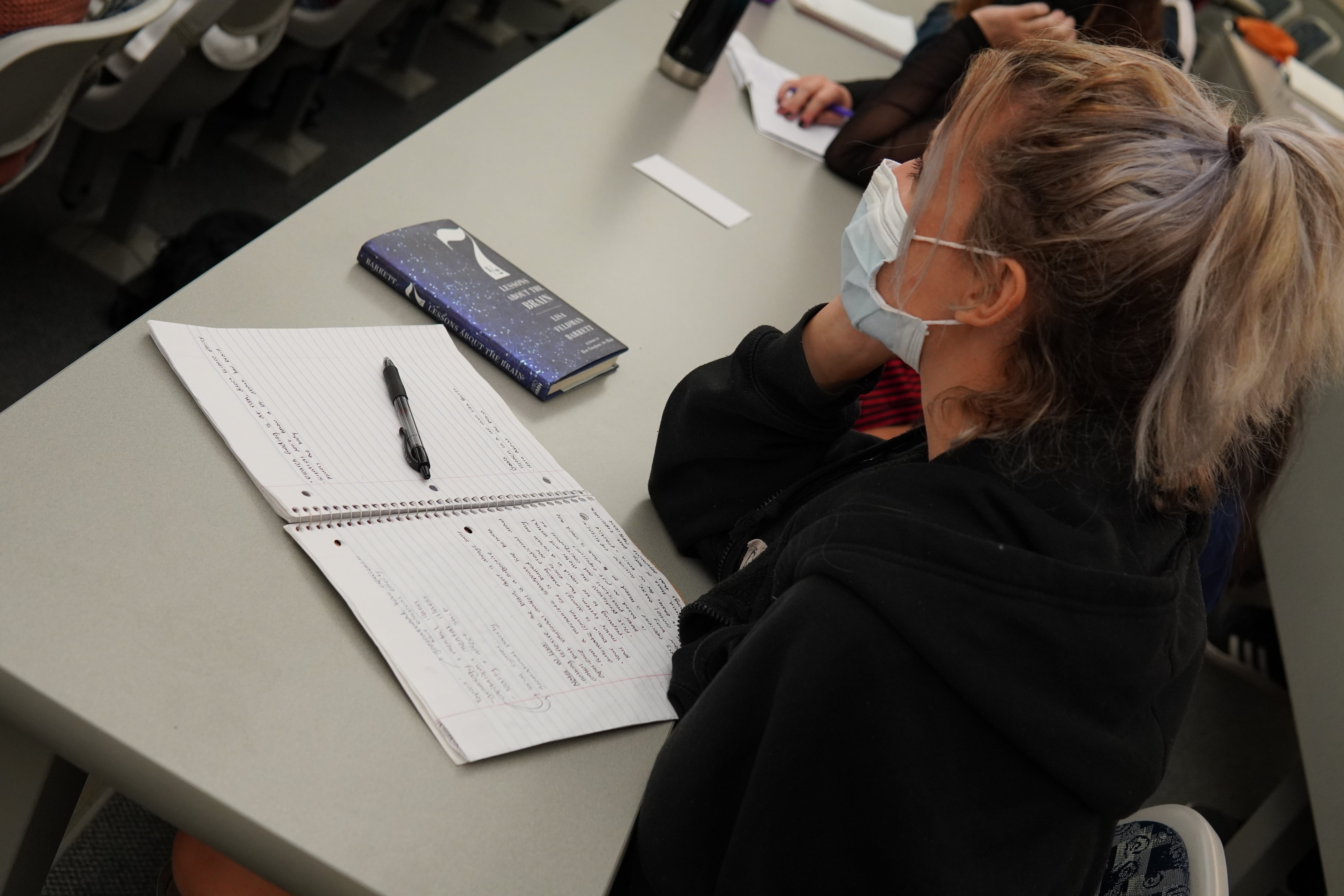 A student leans their arm on a table next to their open notebook and closed copy of